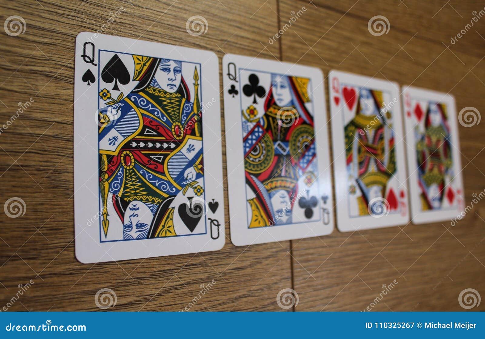 Карточки покера на деревянном backround, комплекте ферзей клубов, диамантах, лопатах, и сердцах