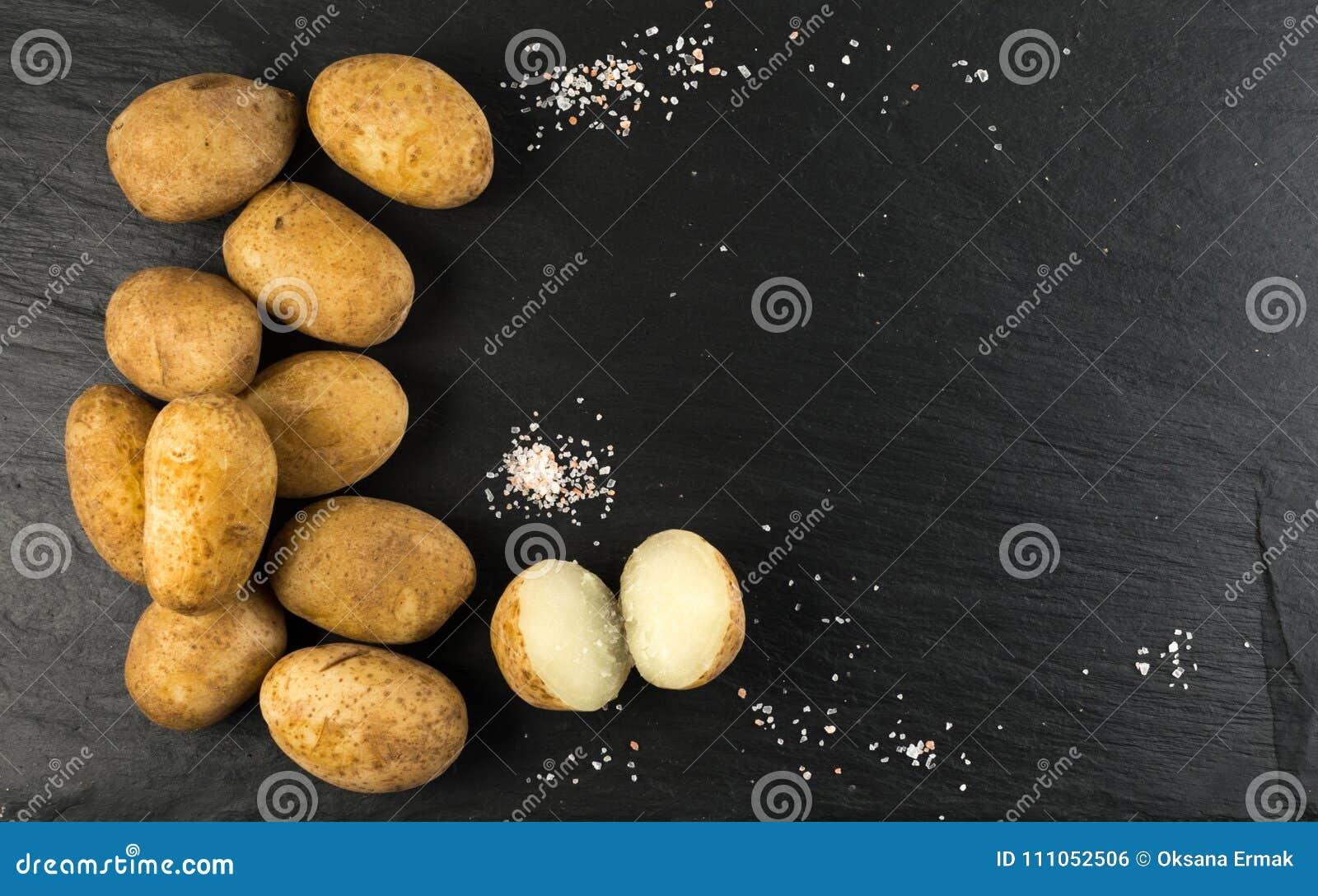 Картошки кипеть в их кожах на каменной предпосылке