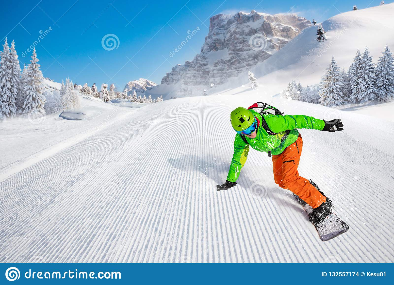 Катание snowboarder человека на наклоне