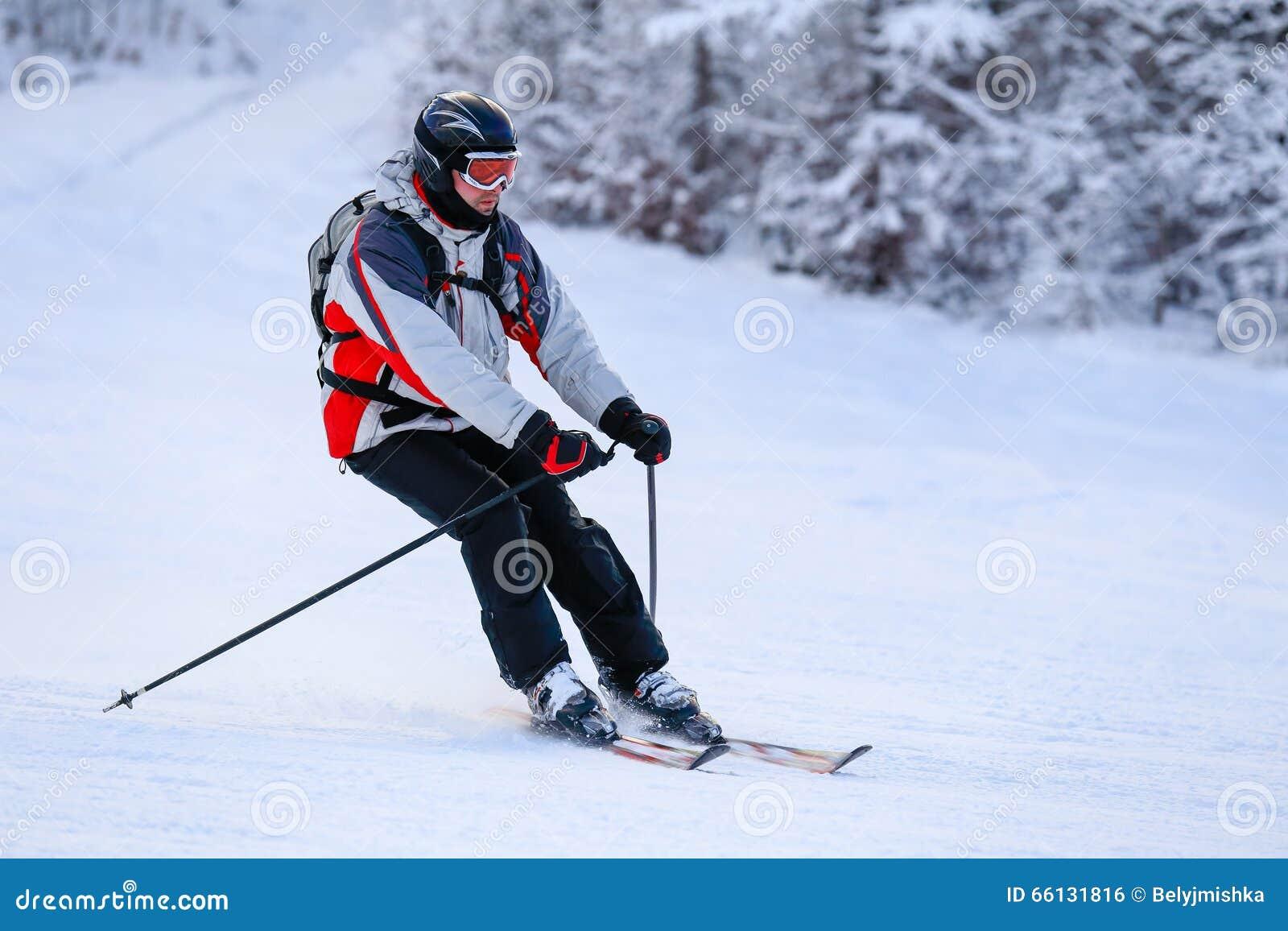 Кататься на лыжах лыжника покатый в горах зимы