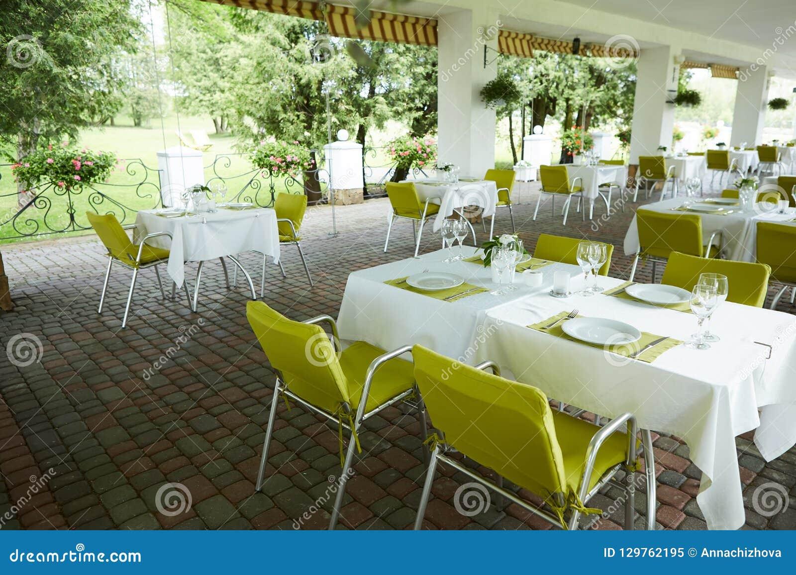 Кафе лета террасы с таблицами и стульями для людей, пустым заведением для воссоздания, никто