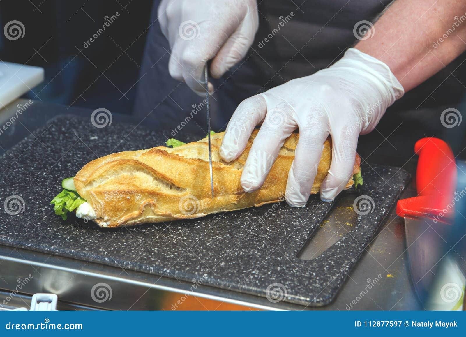 Кашевар в сандвиче отрезков устранимых перчаток