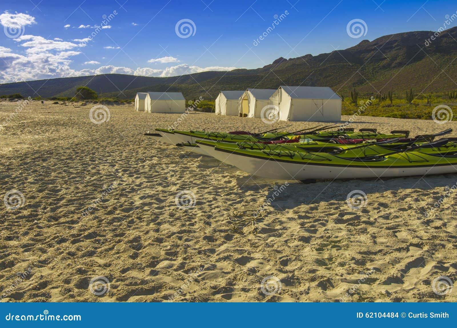 Каяки отдыхают на пляже с располагаясь лагерем шатрами и предпосылкой пустыни