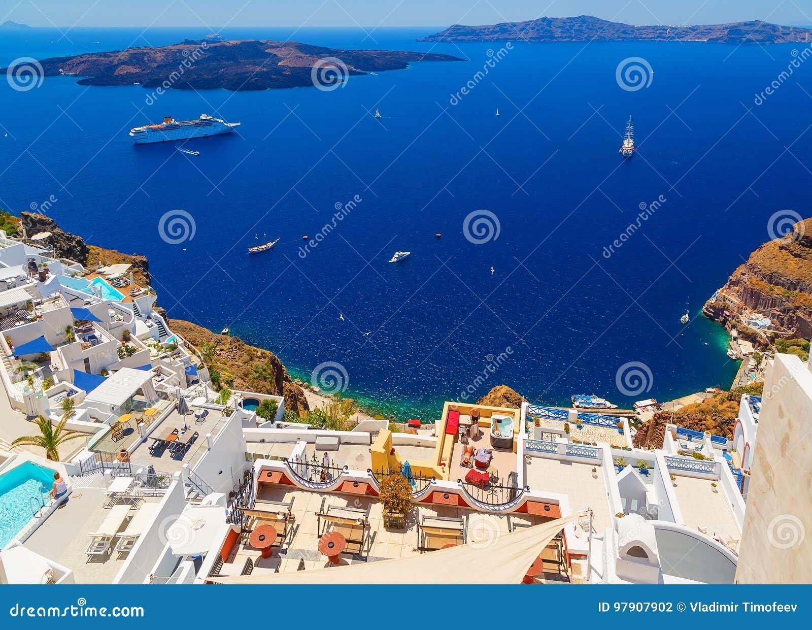 Кальдера Santorini вулканическая как увидено от Fira, столицы Santorini, Греции Гостиницы с отдыхая туристами