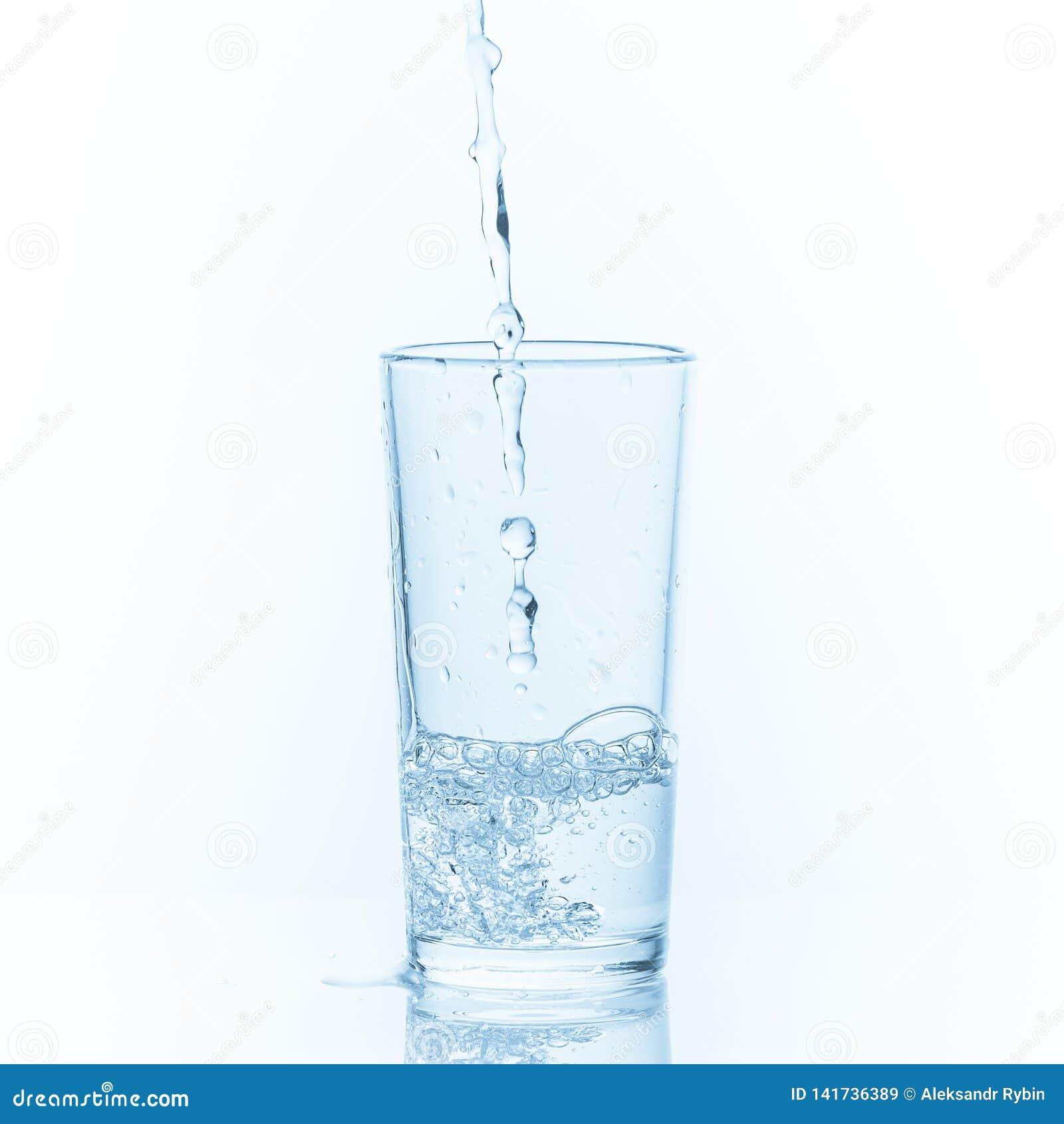 Лить вода в стекло на белой предпосылке