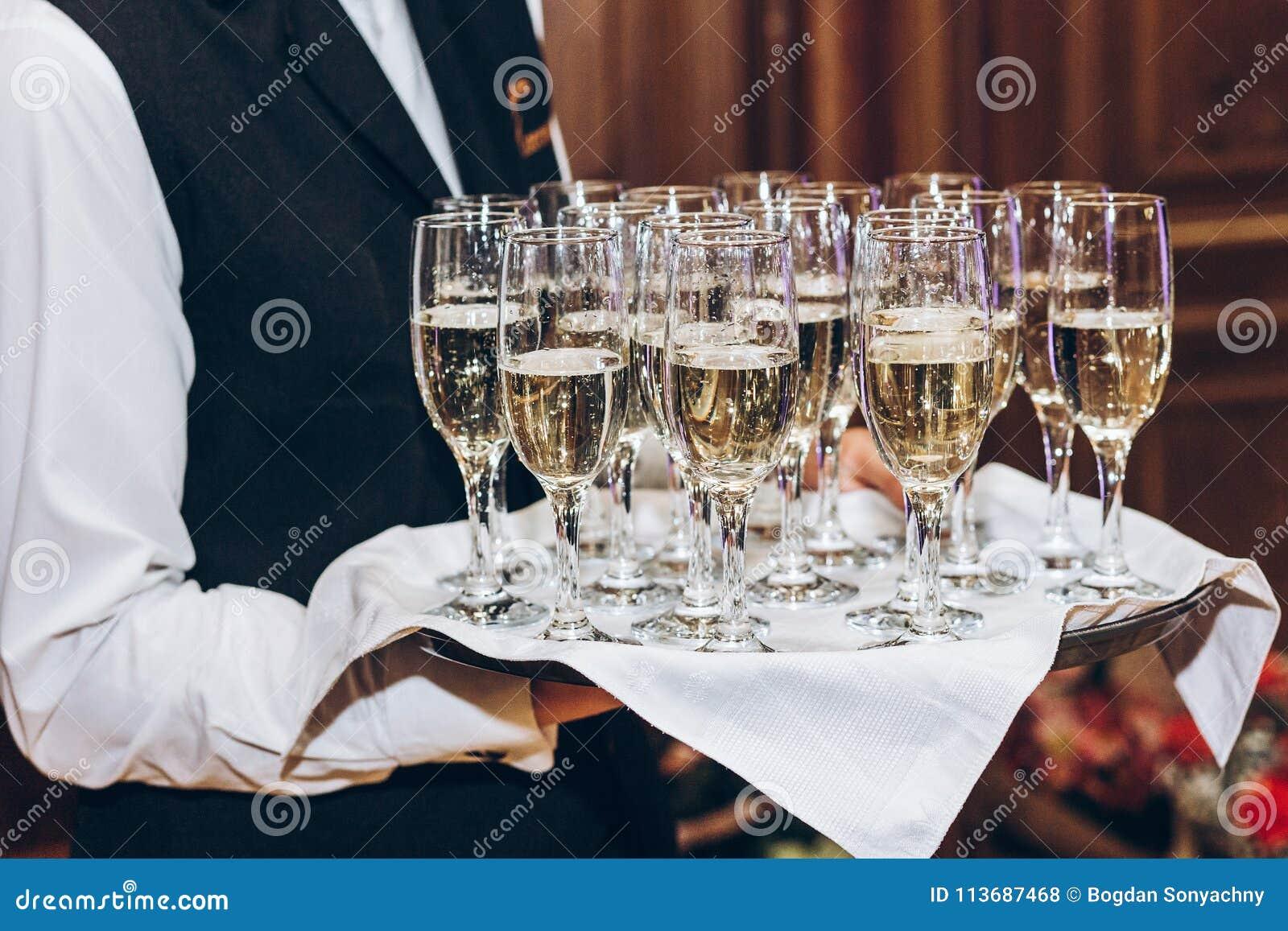 Кельнер служа стильное золотое шампанское в стеклах на подносе Eleg