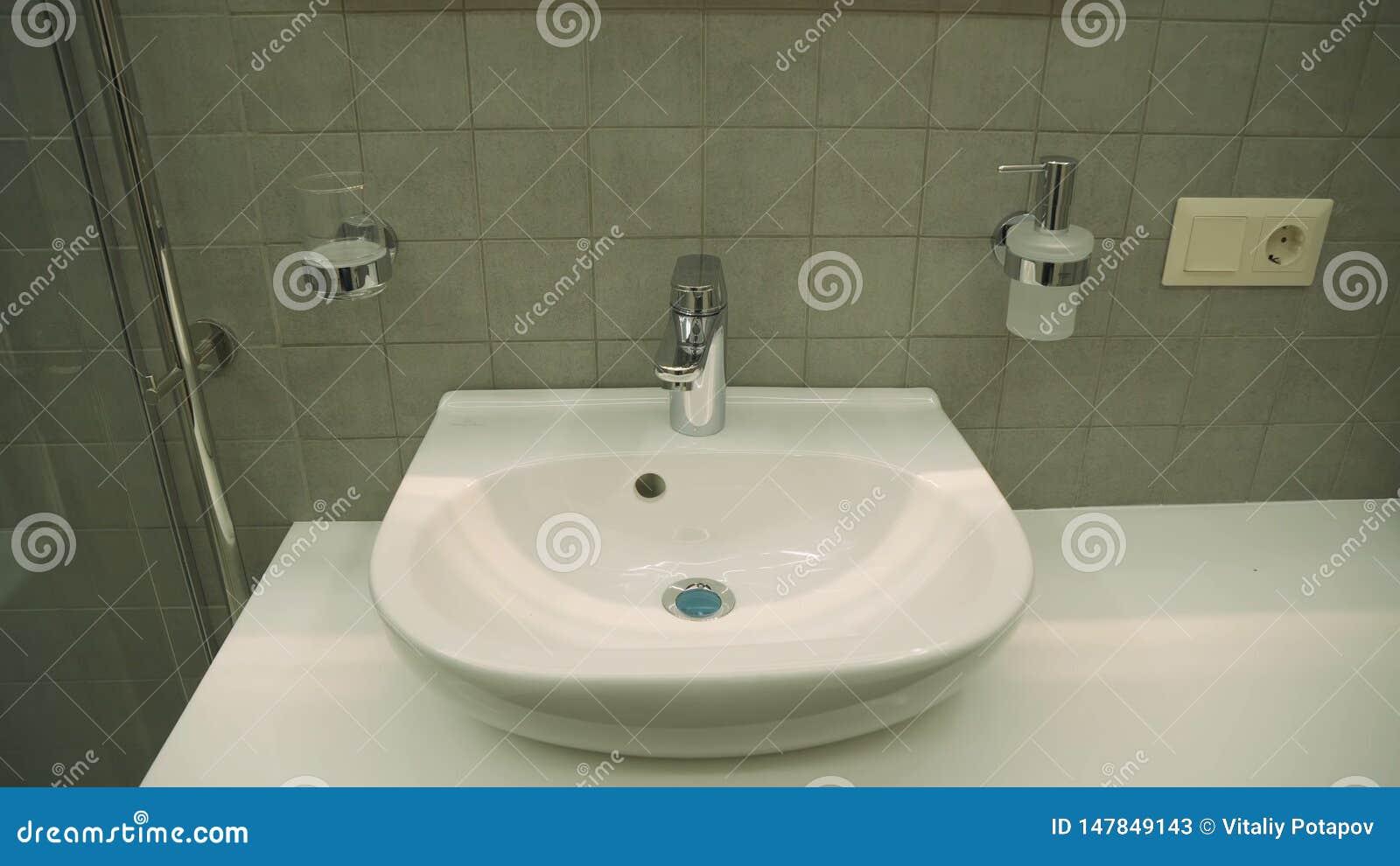 Керамический washbasin с горячим и холодным faucet в bathroom роскошного отеля