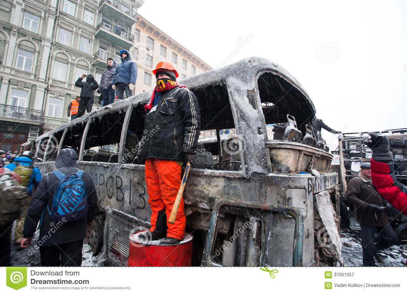 КИЕВ, УКРАИНА: Протестующий с жезлом и шлем смотрят вне, который сгорели улицу около большого сломанного воинского автомобиля