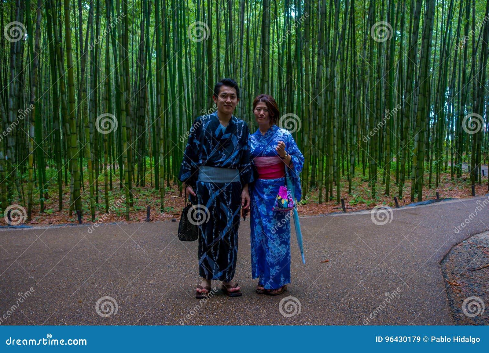 КИОТО, ЯПОНИЯ - 5-ОЕ ИЮЛЯ 2017: Неопознанные пары представляя на камере в пути на красивом бамбуковом лесе на Arashiyama