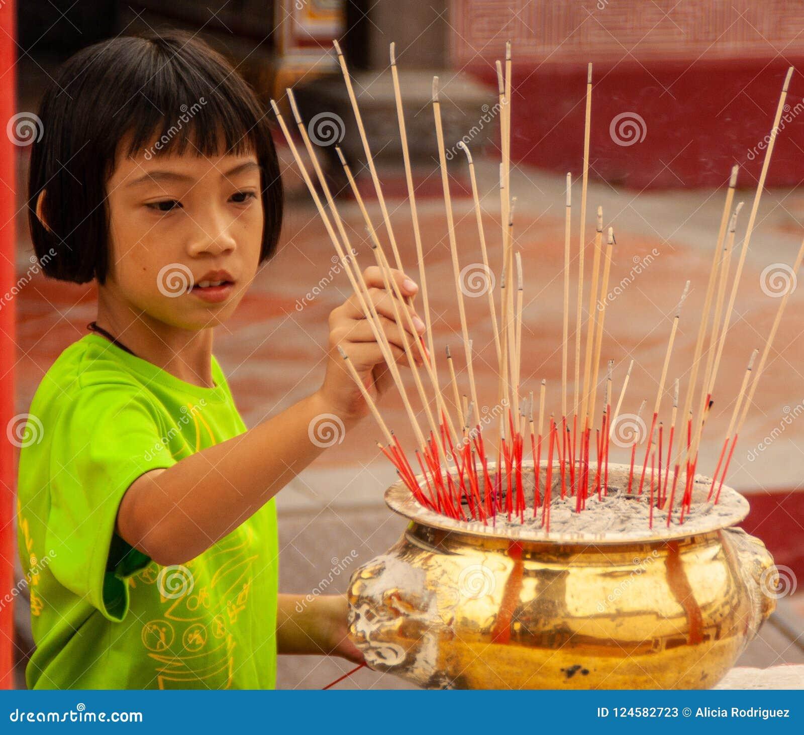 Китайская девушка засаживая inciense в виске в Малакке, Малайзии