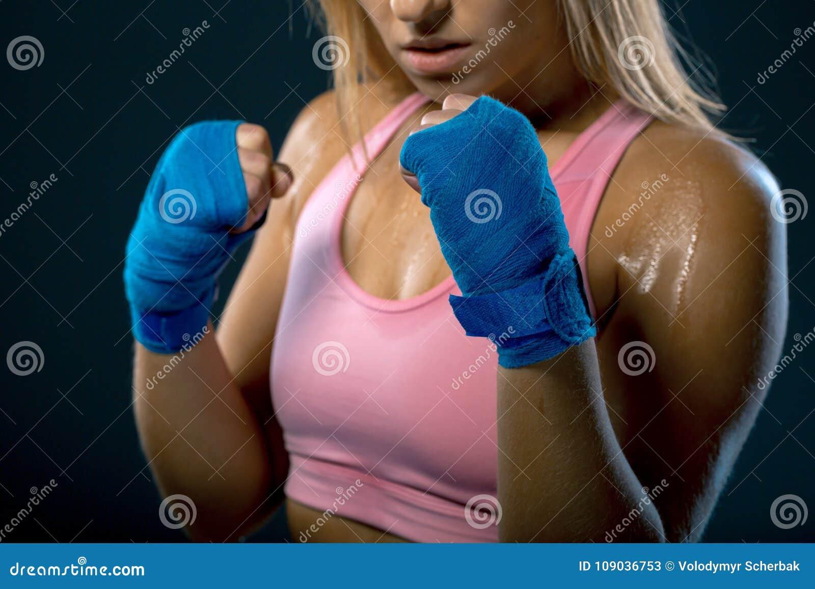 кладя в коробку счастливая женщина усмешки Боец молодой женщины готовый для боя сильная женщина Женские руки обернутые в повязке