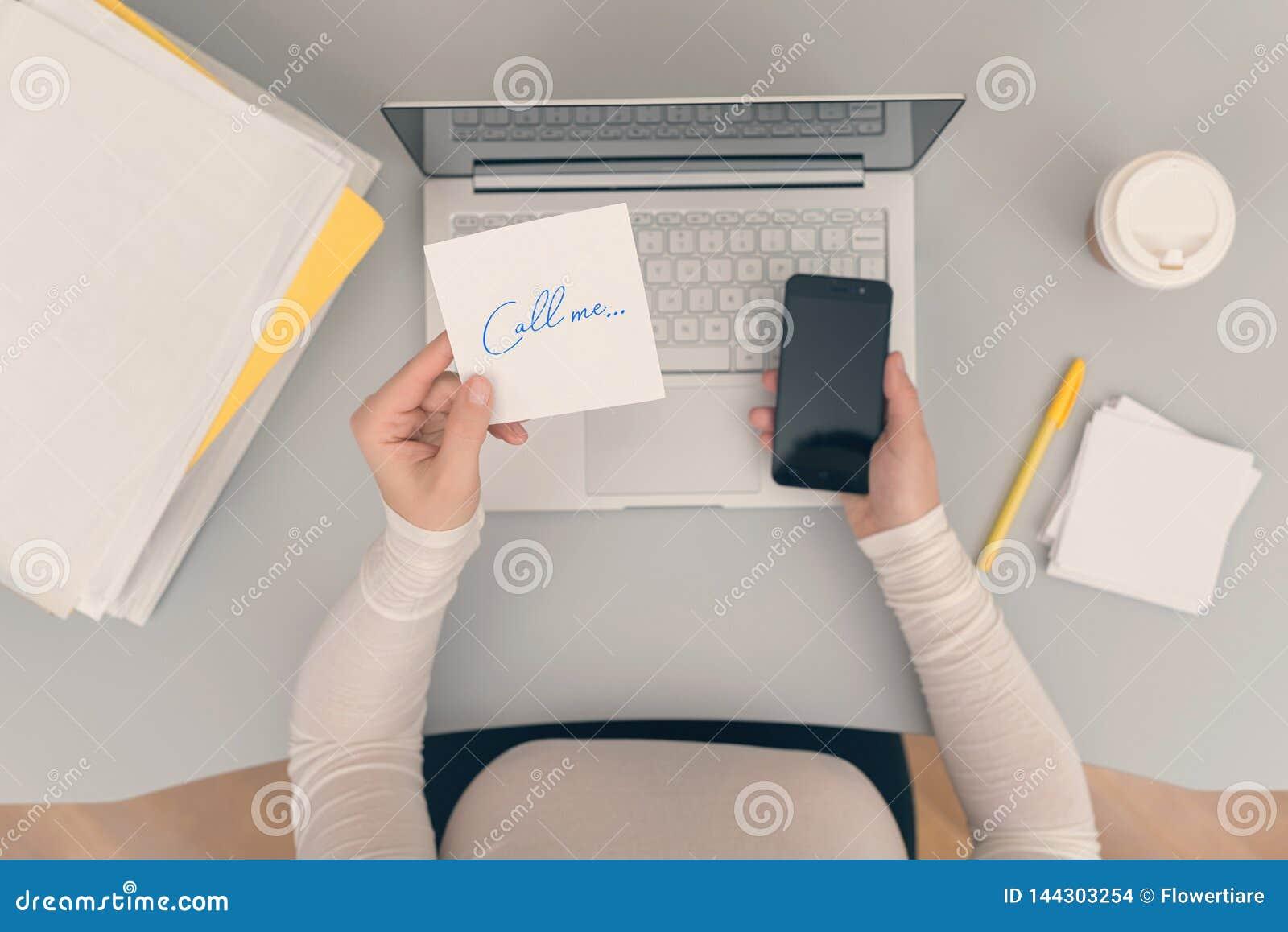 Клерк женщины в офисе держа стикер бумаги со словом вызывает меня r