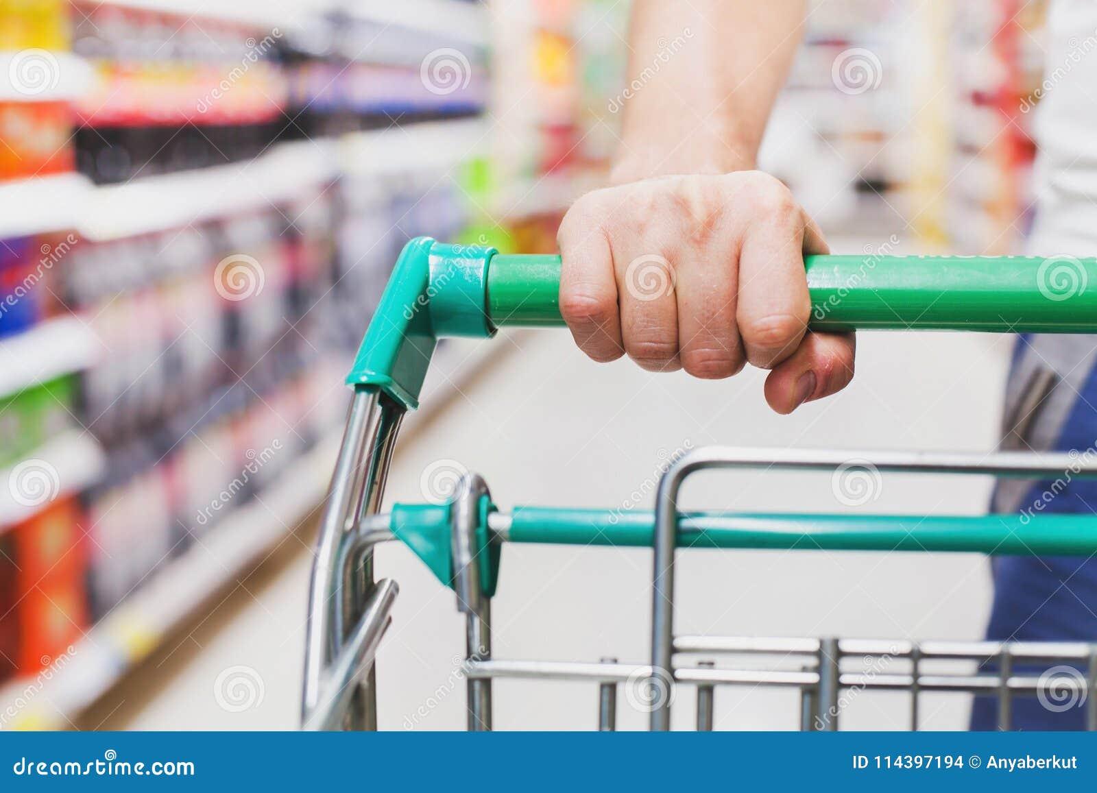 Клиент с магазинной тележкаой в супермаркете