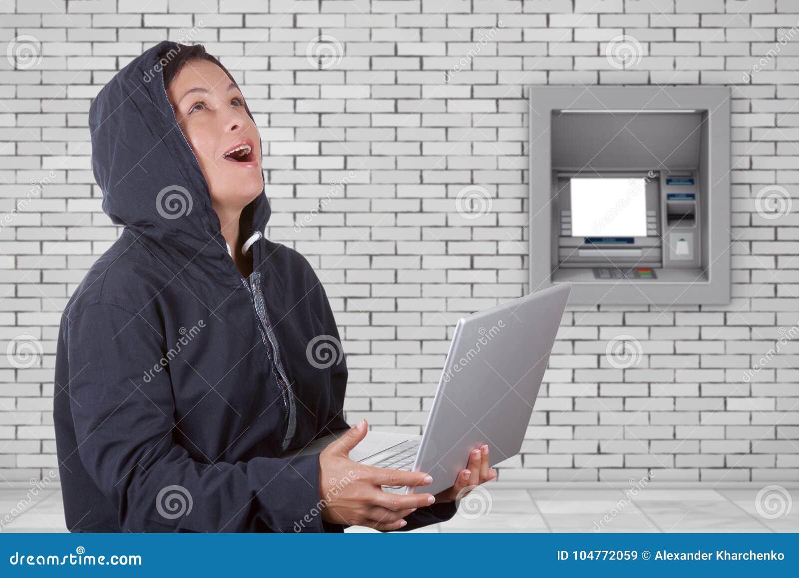 Клобук уголовного хакера женщины нося на использовании компьтер-книжки перед