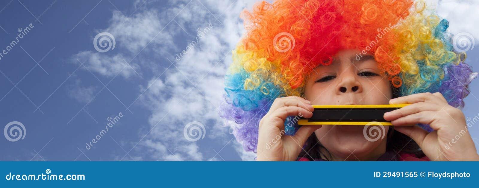 Клоун малыша играя губную гармонику