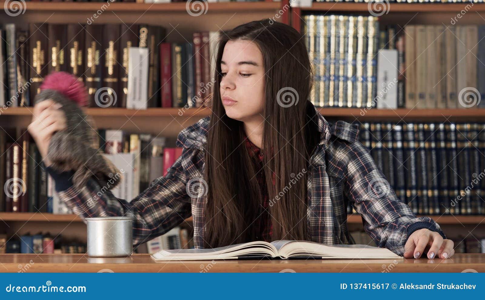 Книга чтения девушки студента в университетской библиотеке акции видеоматериалы