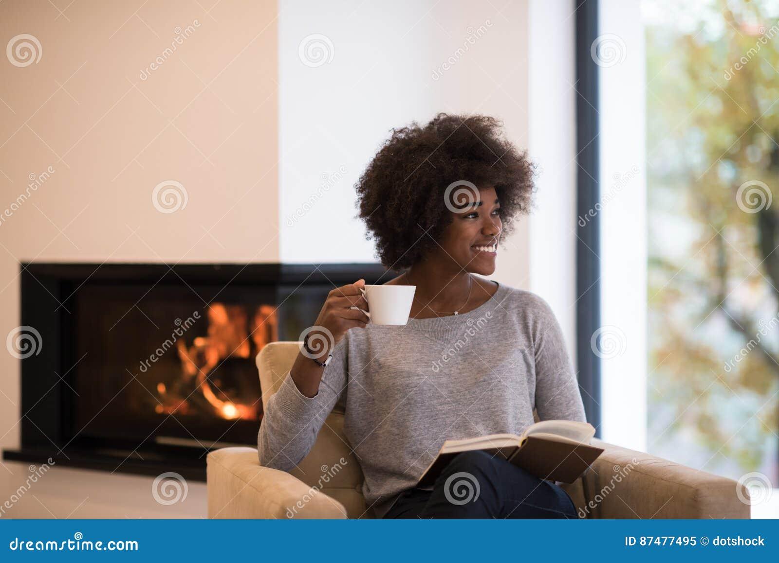 Книга чтения чернокожей женщины перед камином