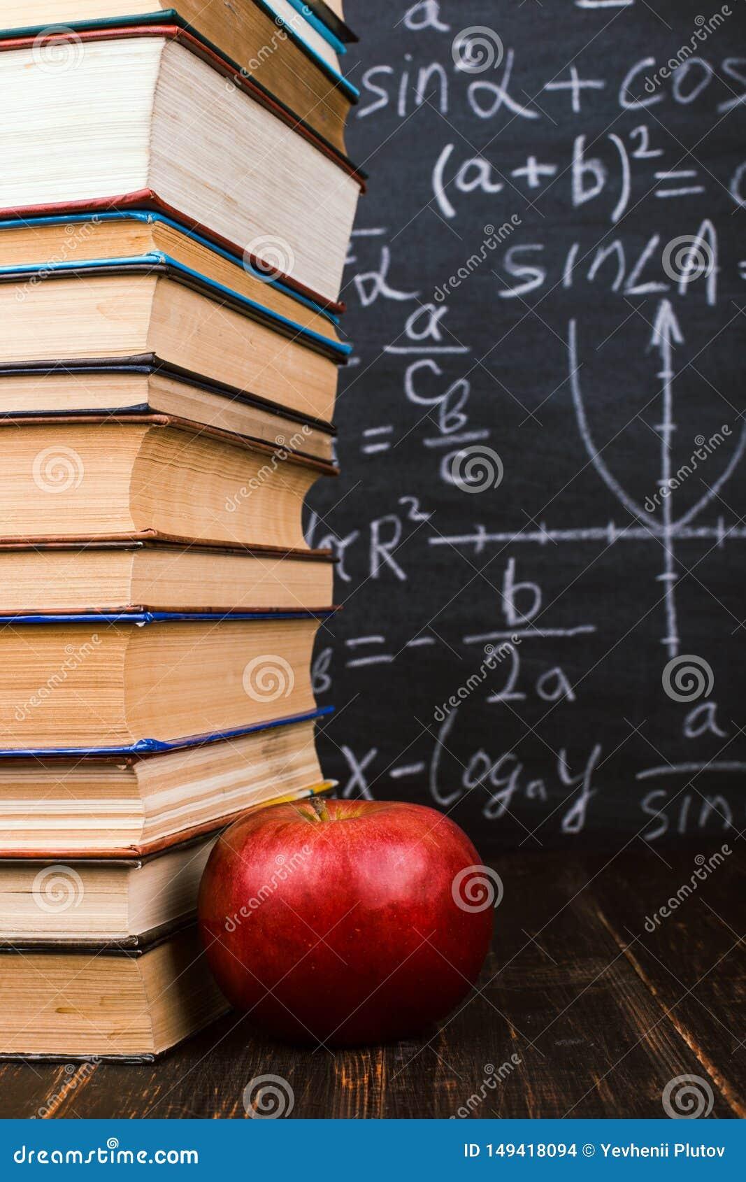 Книги и яблоко на деревянном столе, на фоне доски с формулами Teacher' концепция дня s и назад к