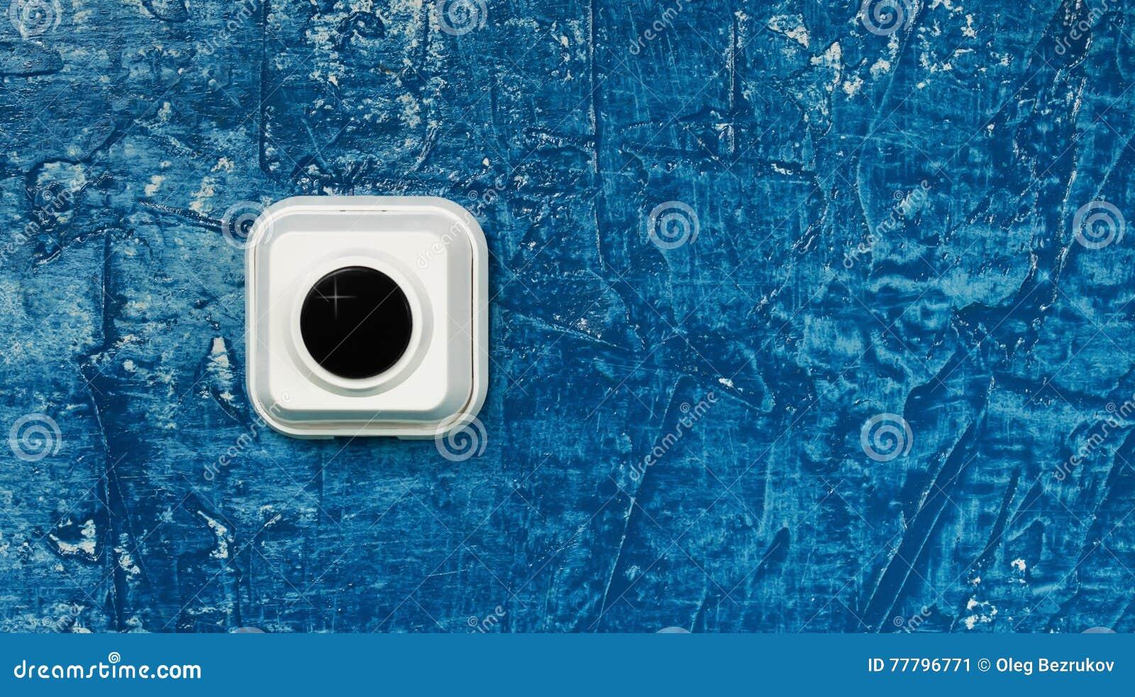 Кнопка звонка на голубой стене