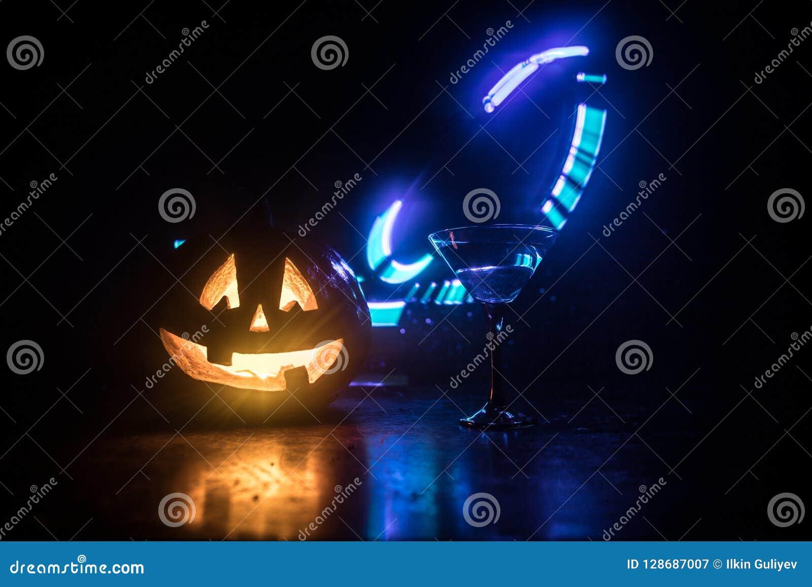 Коктеили апельсина тыквы хеллоуина питье праздничное Партия Halloween Смешная тыква с накаляя стеклом коктеиля на темноте тонизир