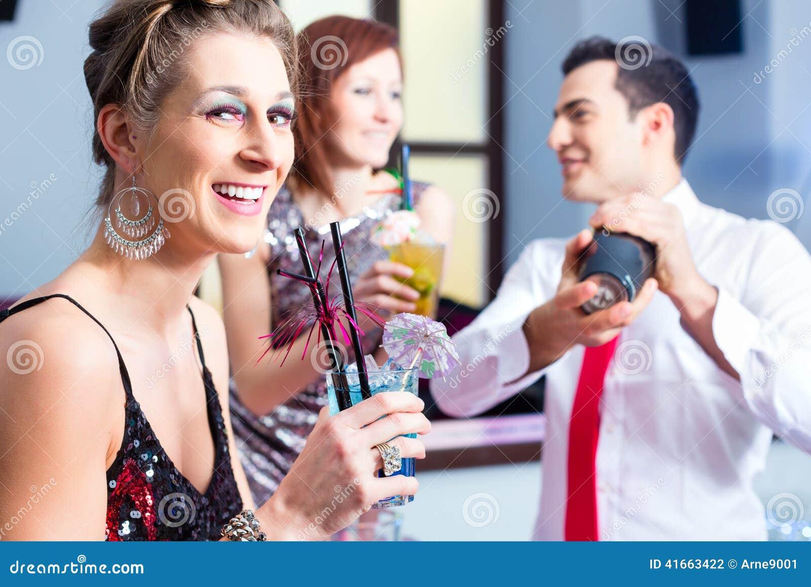 Коктеили женщины выпивая в коктейль-баре