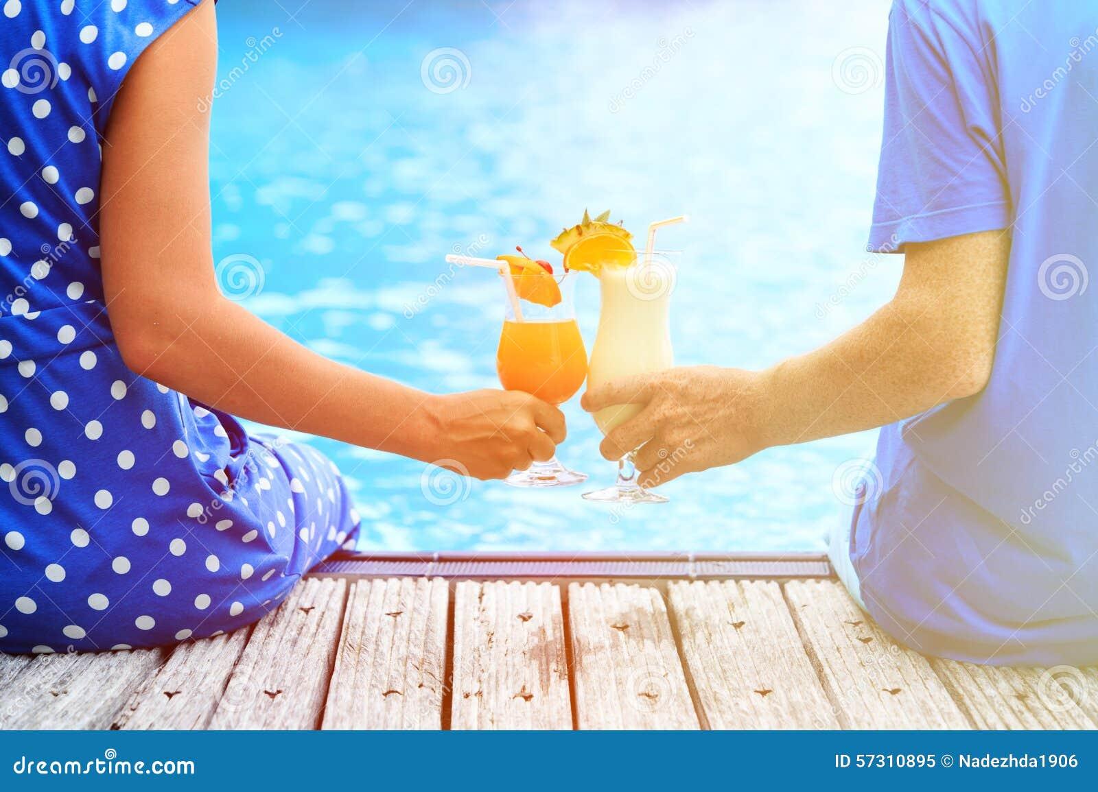 Коктеили пар выпивая приближают к бассейну или пляжу