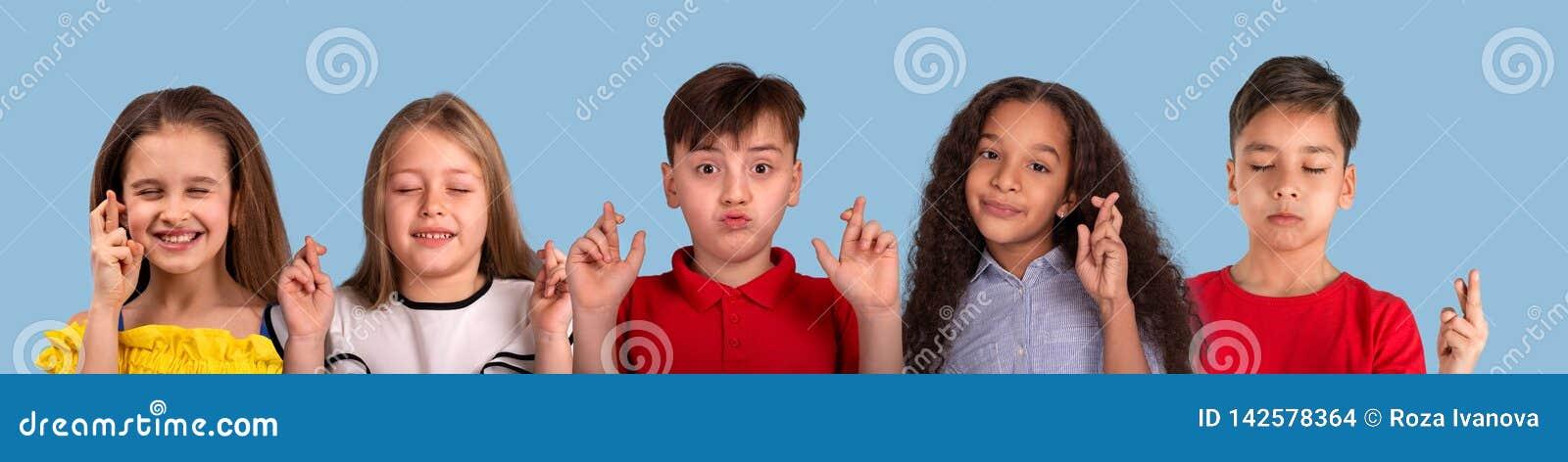 Коллаж портретов эмоции студии Мульти-этнической группы в составе школьник, на голубой предпосылке