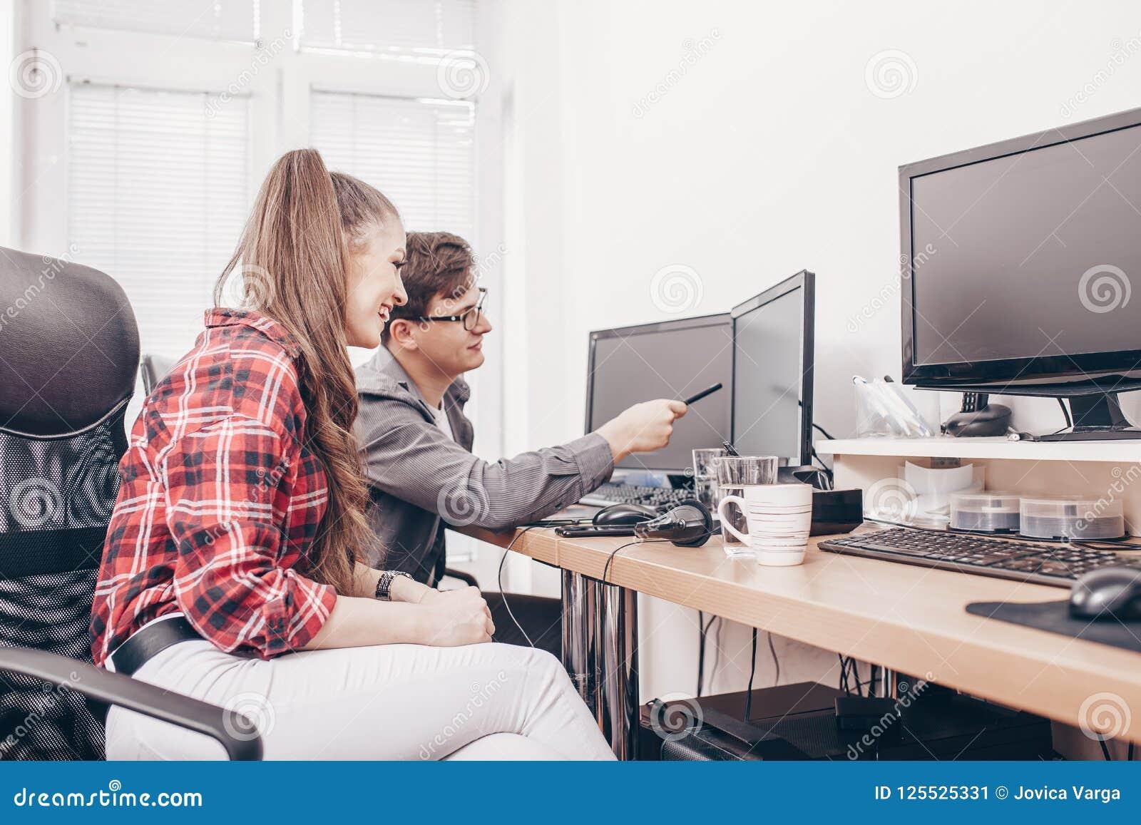 Коллеги в офисе работая на настольном компьютере