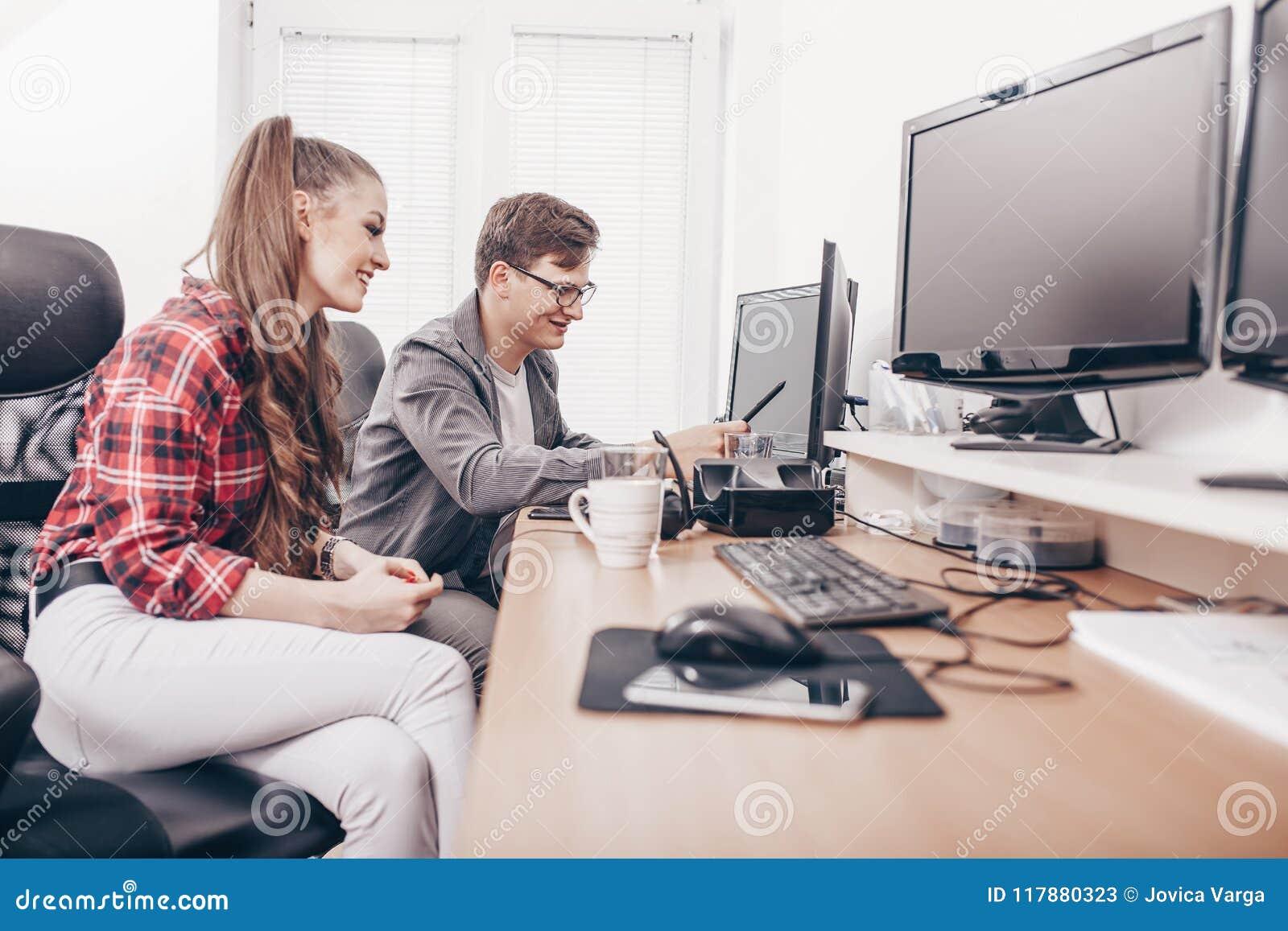 Коллеги работая на настольном компьютере