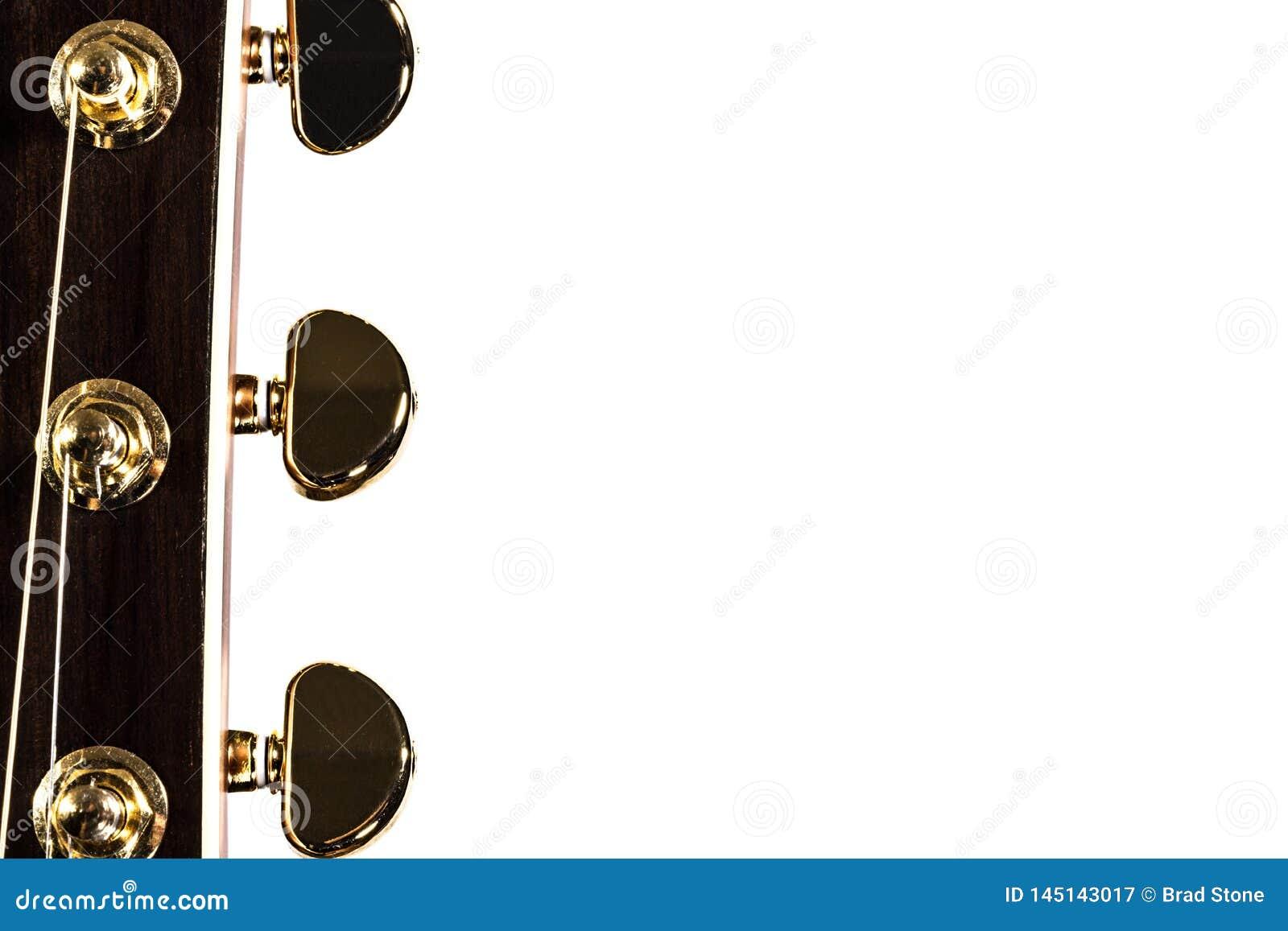 Колышки гитары настраивая на белой предпосылке