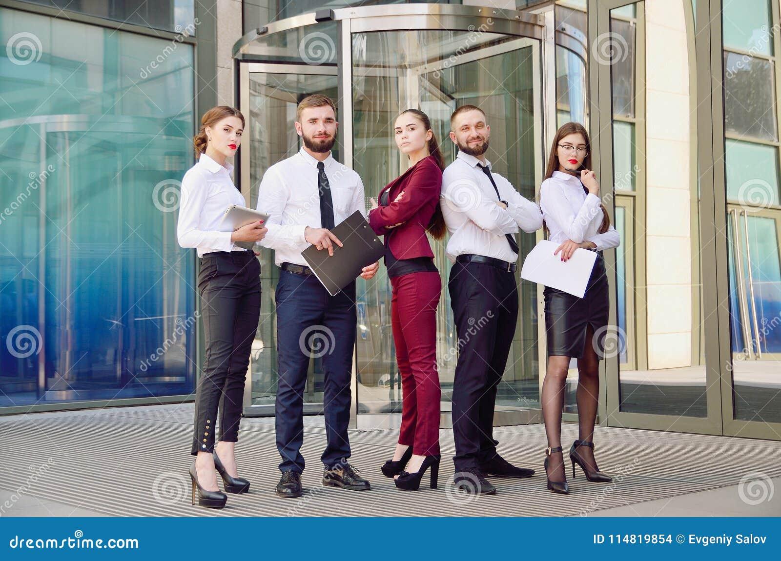 команда Молодые работники офиса на предпосылке мульти-магазина