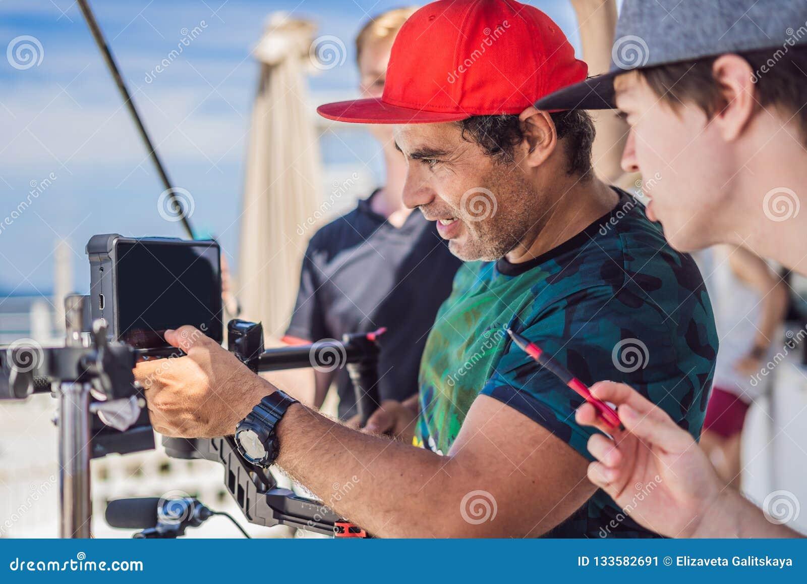 Команда продукции на коммерчески видео- всходе Оператор Steadicam использует стабилизатор и кино-степень камеры 3 осей