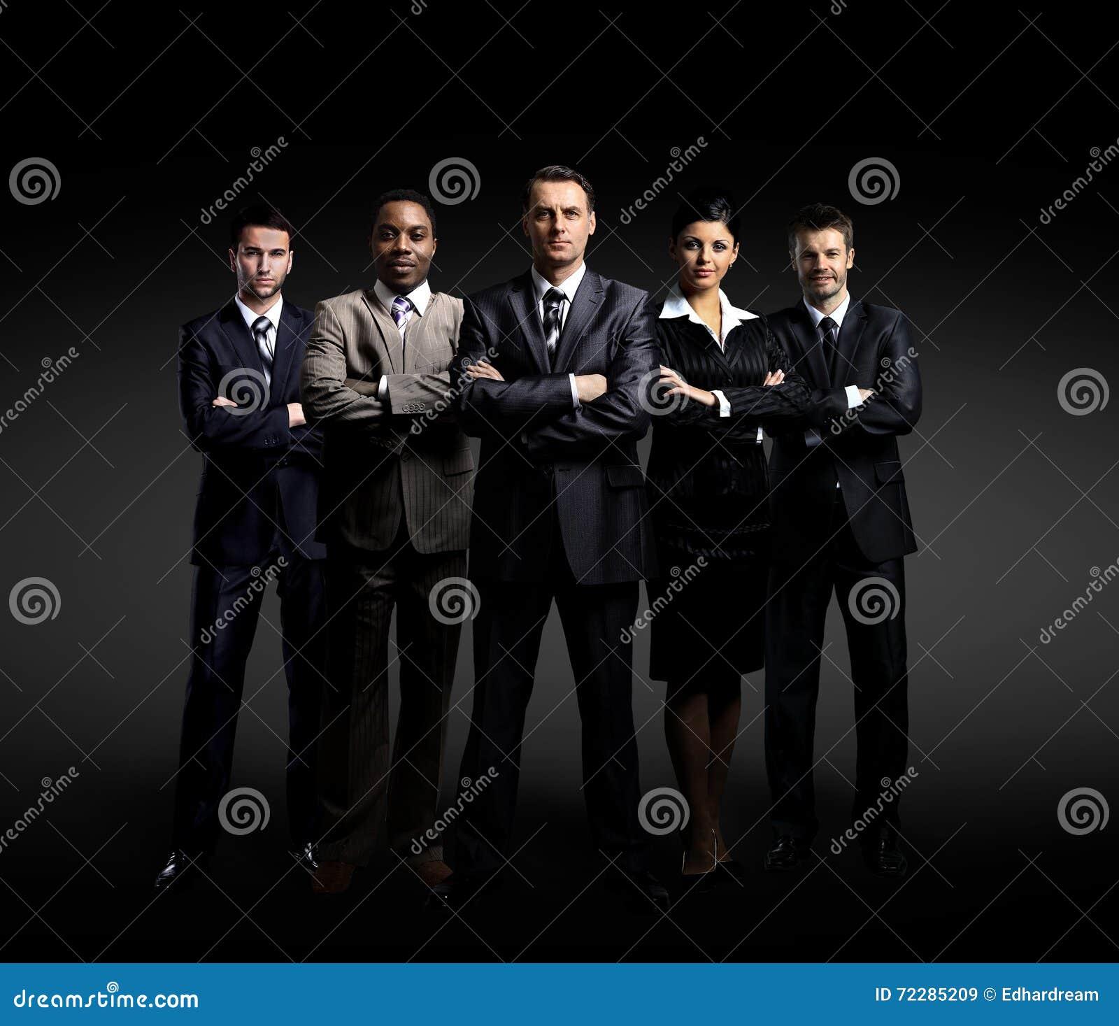 Download Команда дела стоя над темной предпосылкой Стоковое Изображение - изображение насчитывающей женщина, черный: 72285209