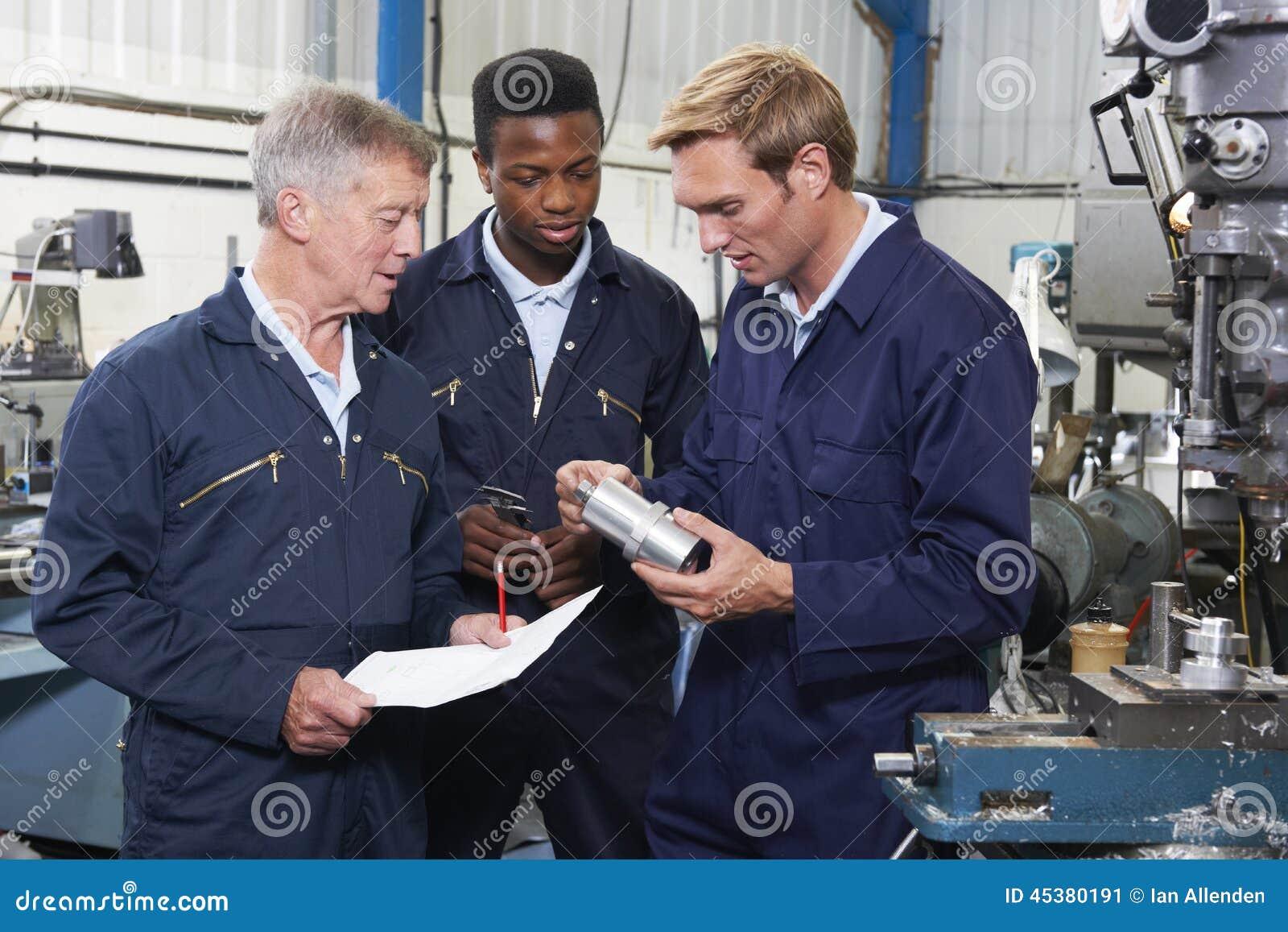 Команда инженеров имея обсуждение в фабрике