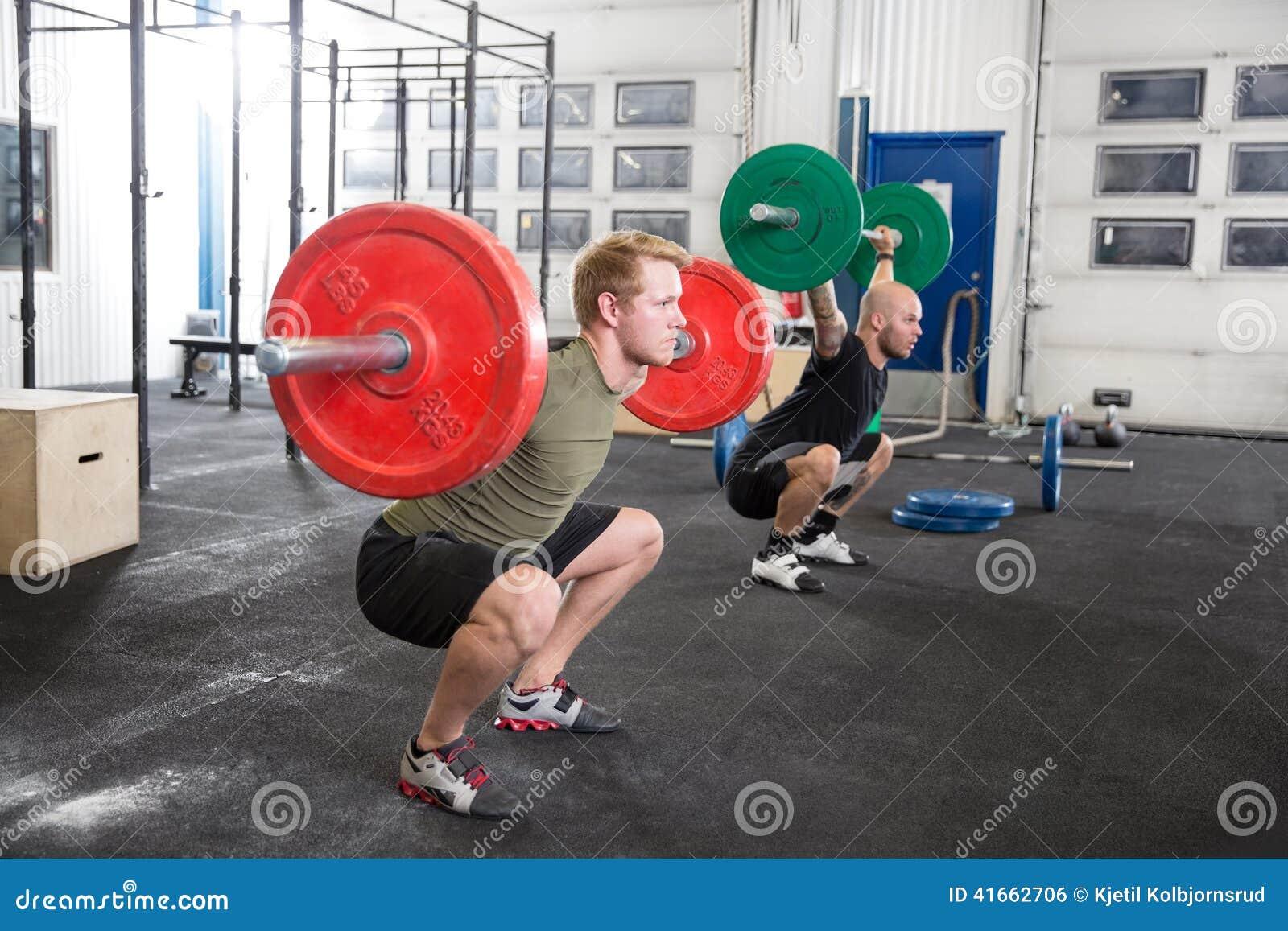 Команда тренирует сидения на корточках в центре спортзала фитнеса