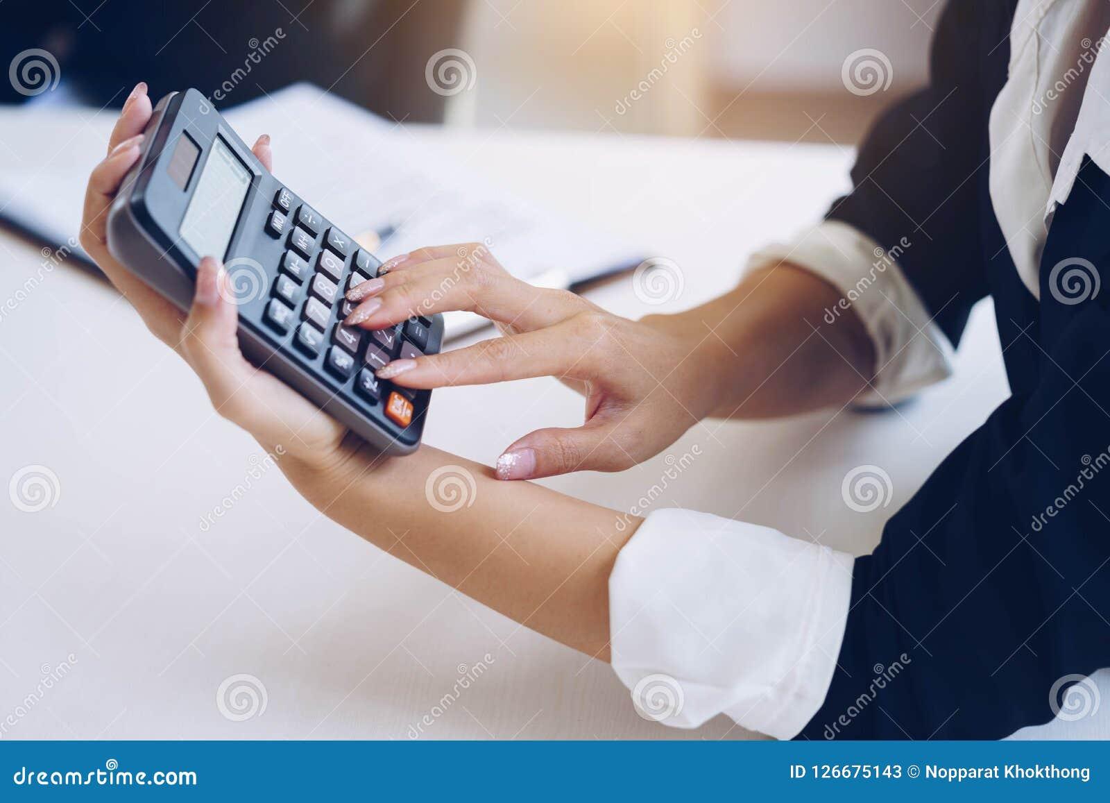 Коммерсантка держа калькулятор для высчитывает номер и диск