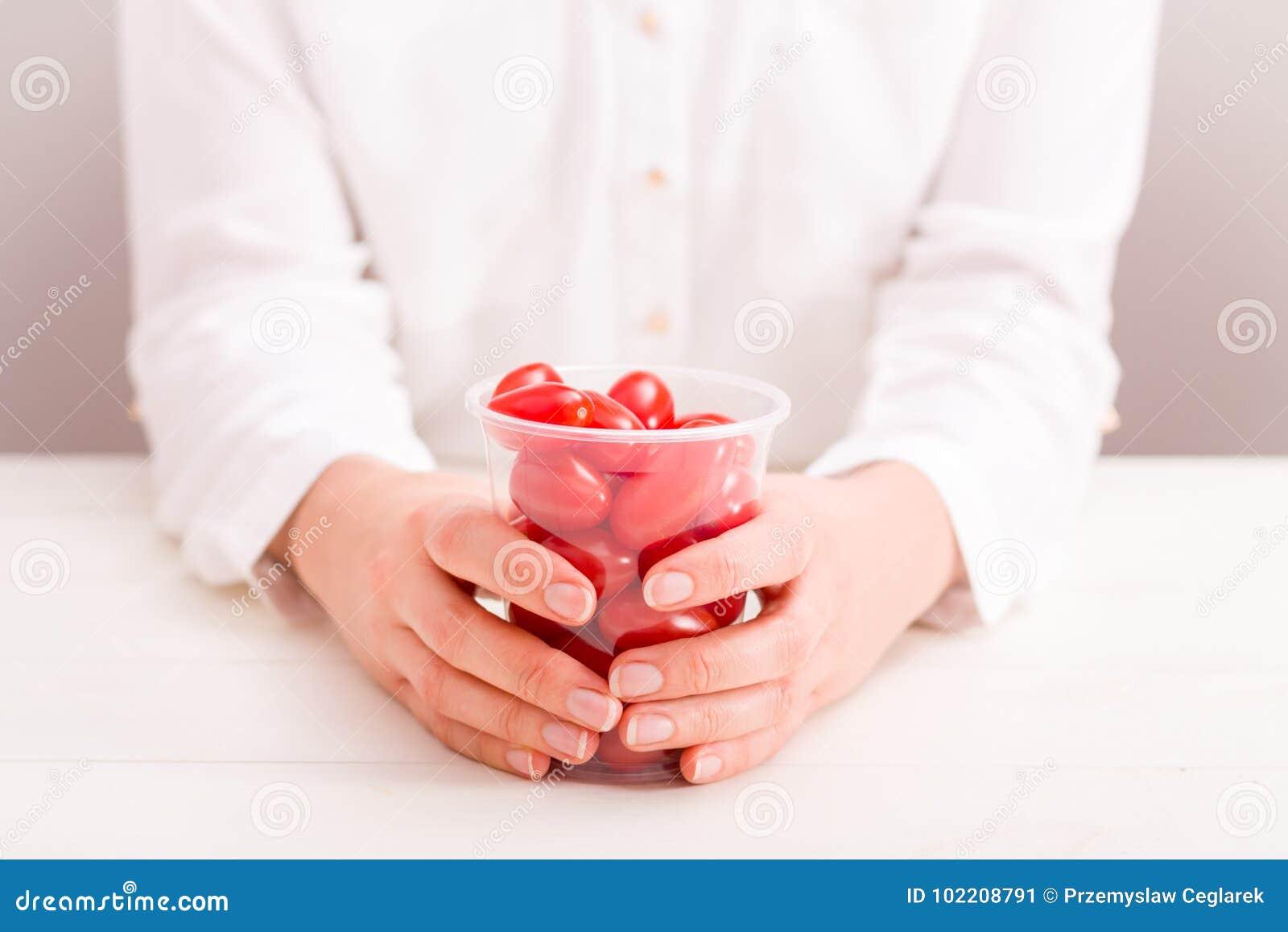 Коммерсантка держа чашку с свежими малыми томатами