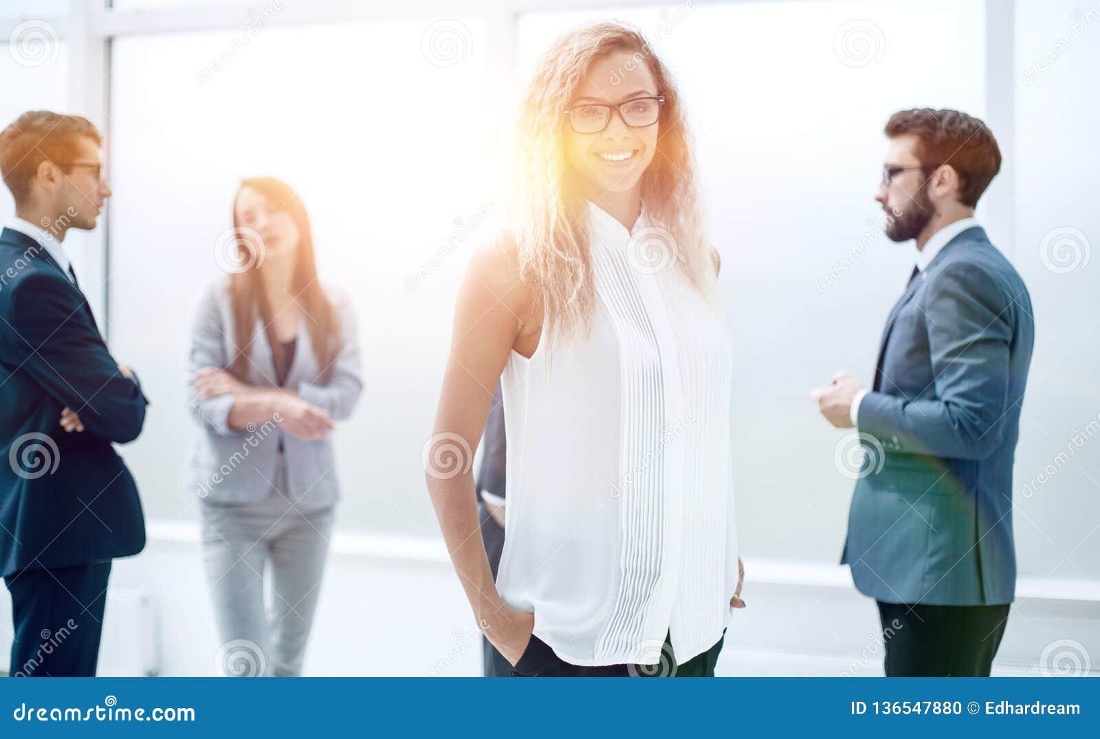Коммерсантка и ее коллеги стоя в офисе
