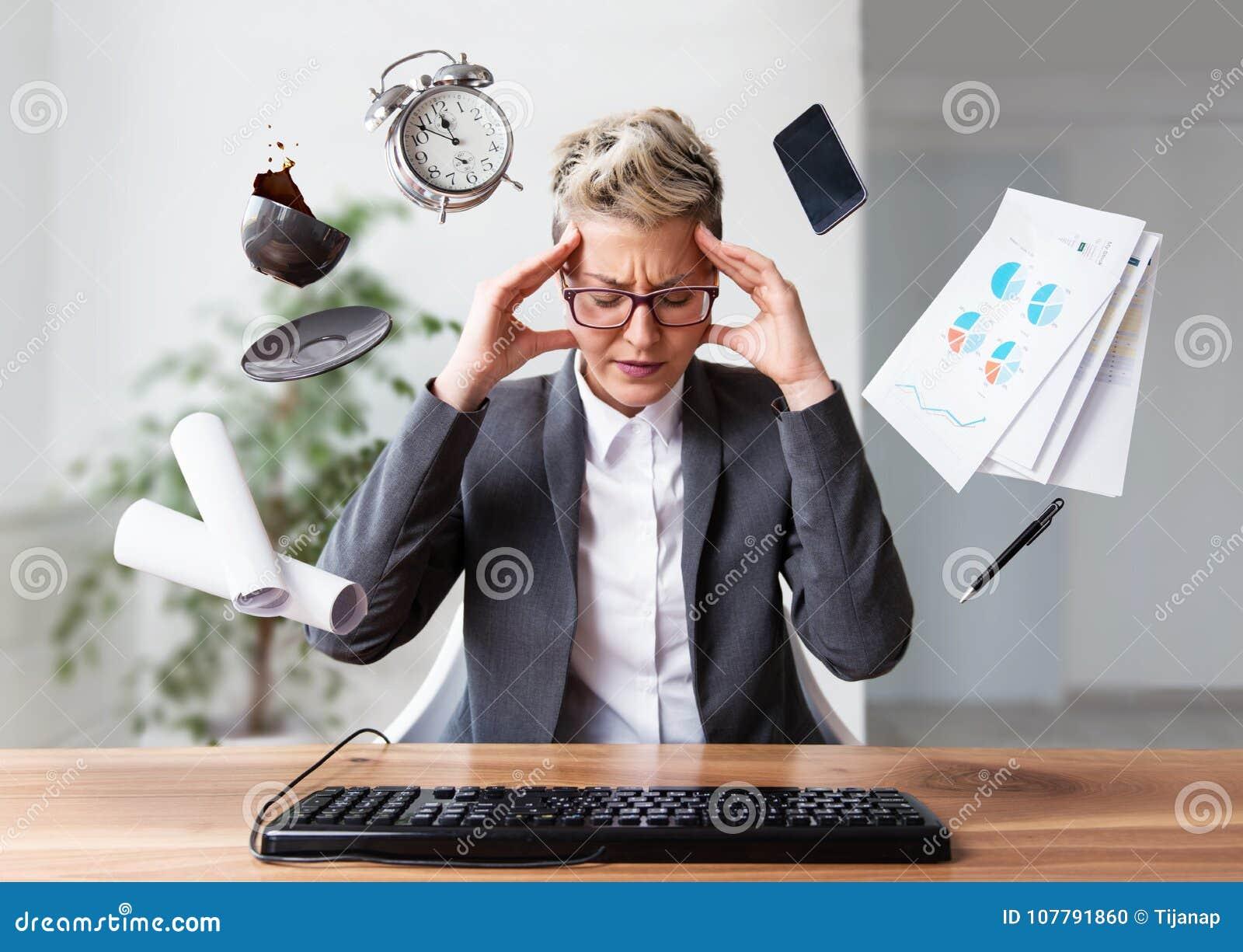 Коммерсантка работая на компьтер-книжке, перегружая, под давлением