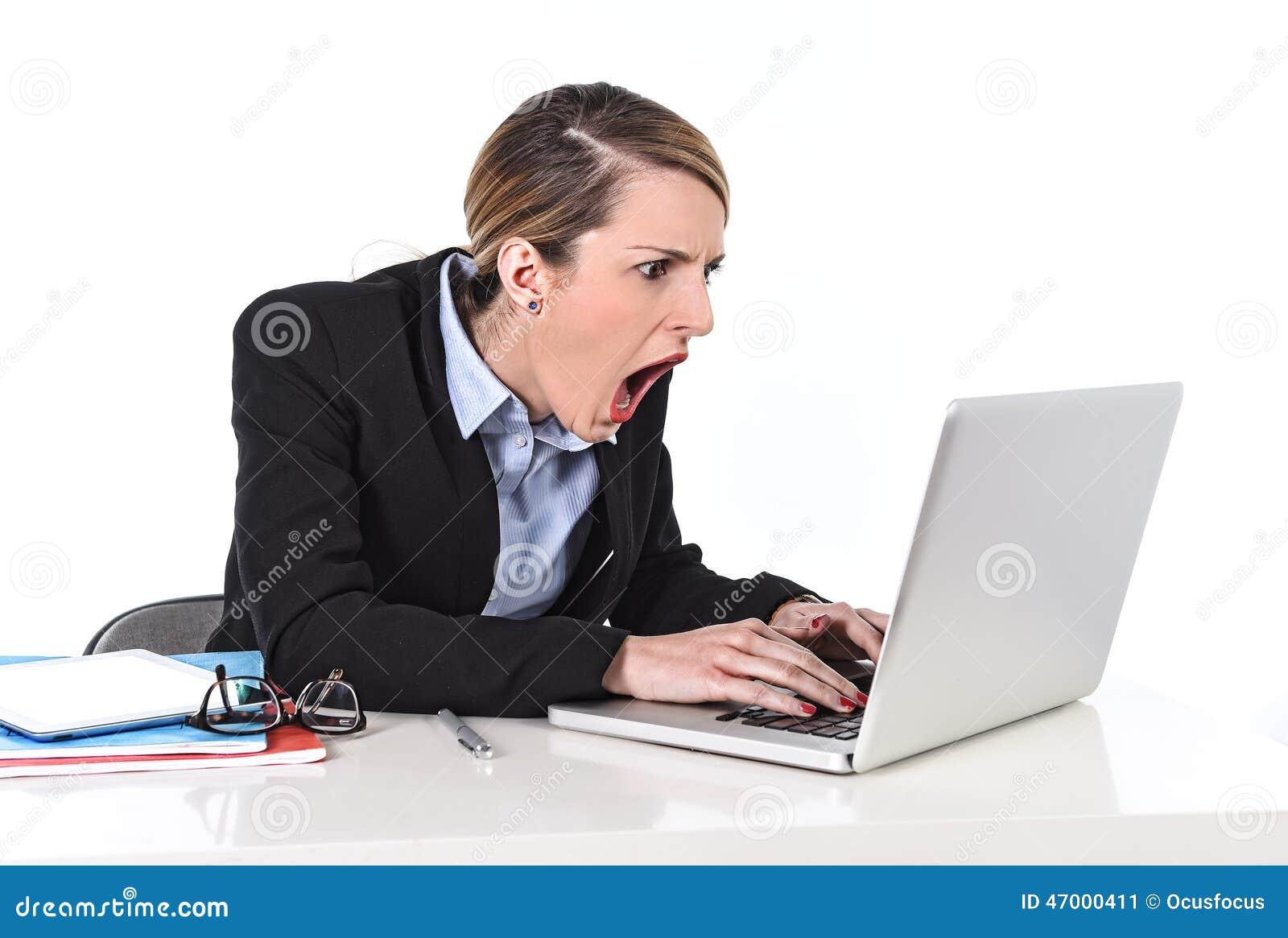 Коммерсантка сидя на столе офиса работая с компьтер-книжкой в стрессе смотря расстроенный