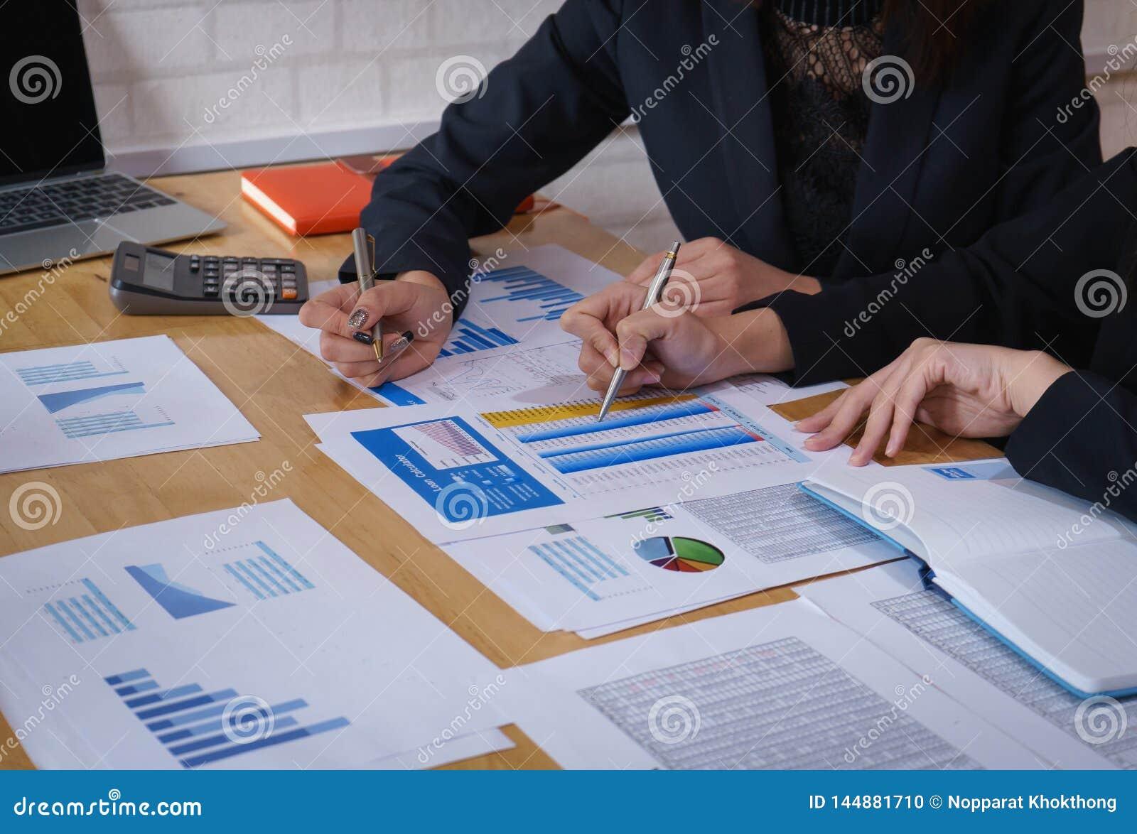Коммерсантка указывая ручка на деловом документе на конференц-зал Диаграммы и диаграммы данным по обсуждения и анализа показывая