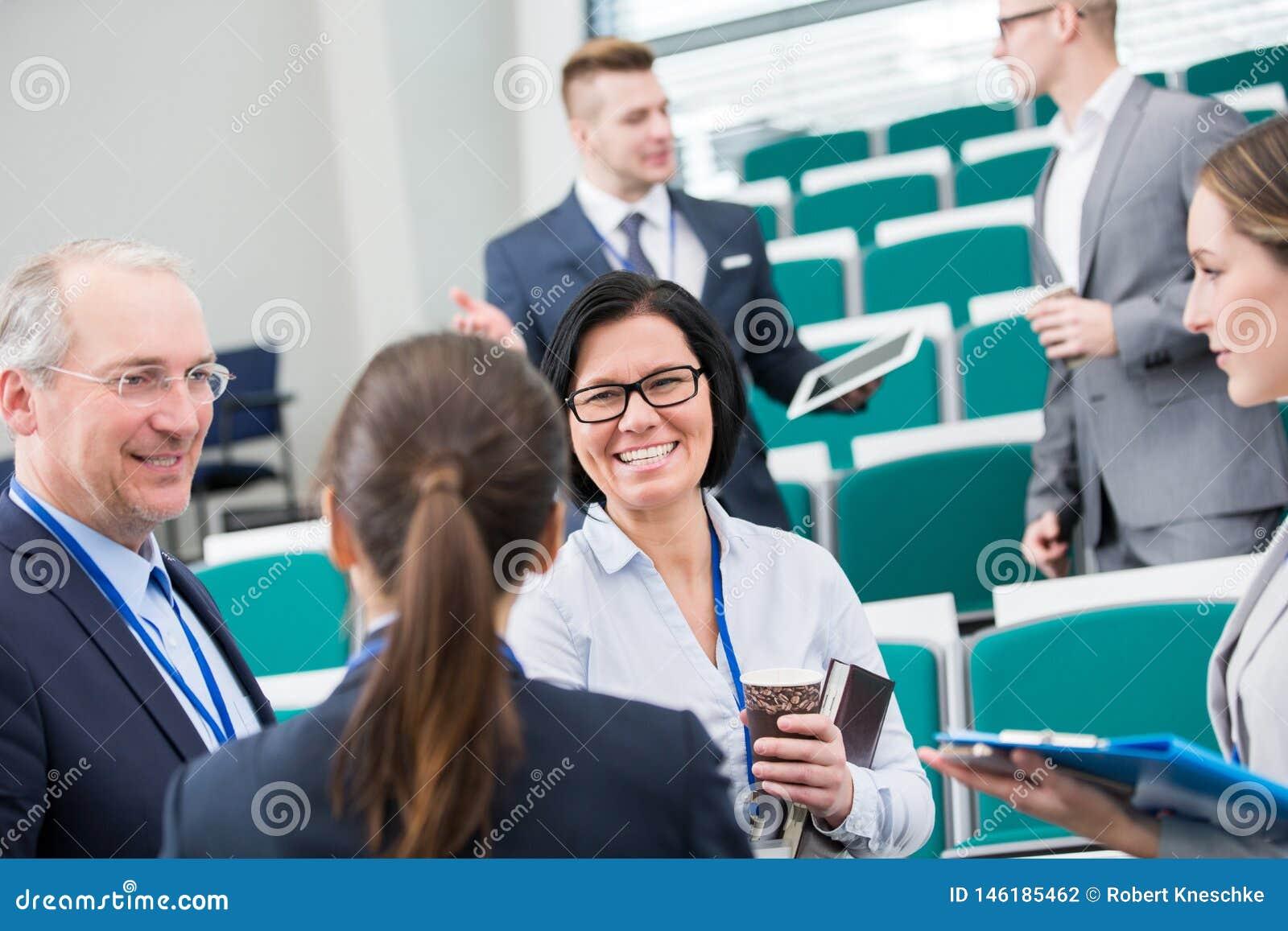 Коммерсантка усмехаясь пока связывающ с коллегами