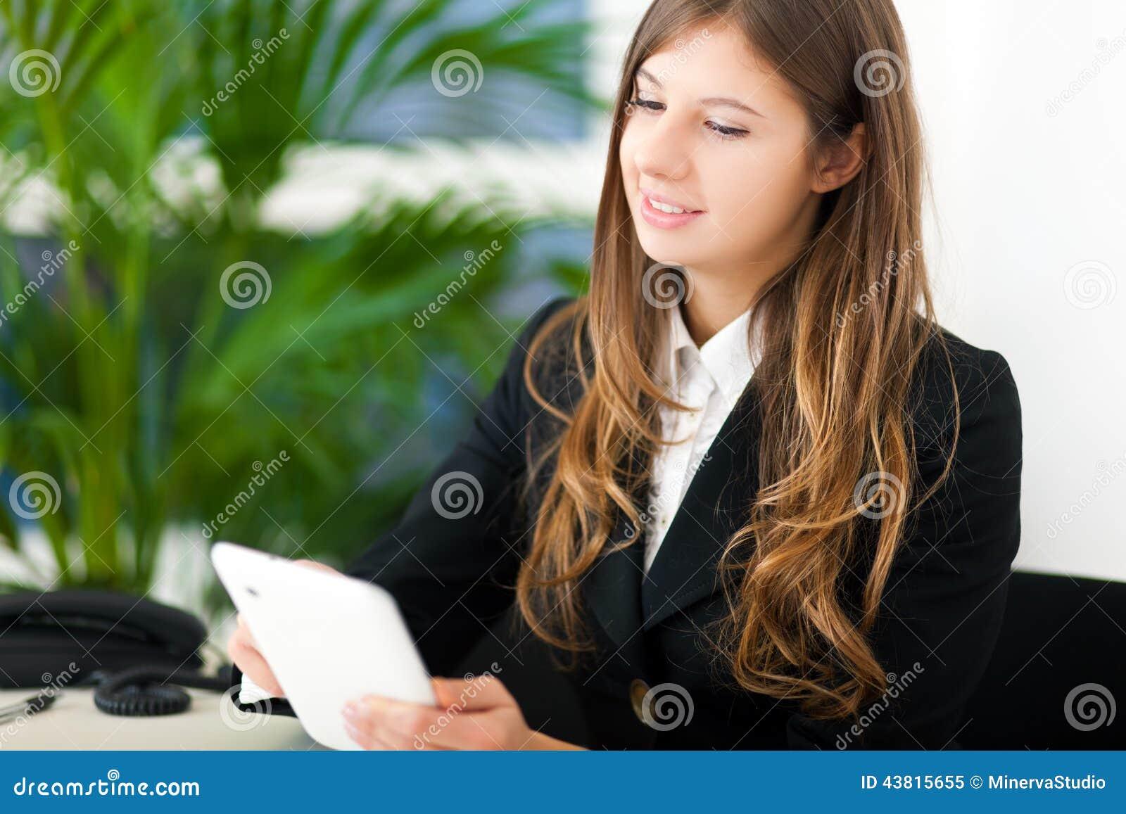 Коммерсантка Youngn используя ее планшет в офисе