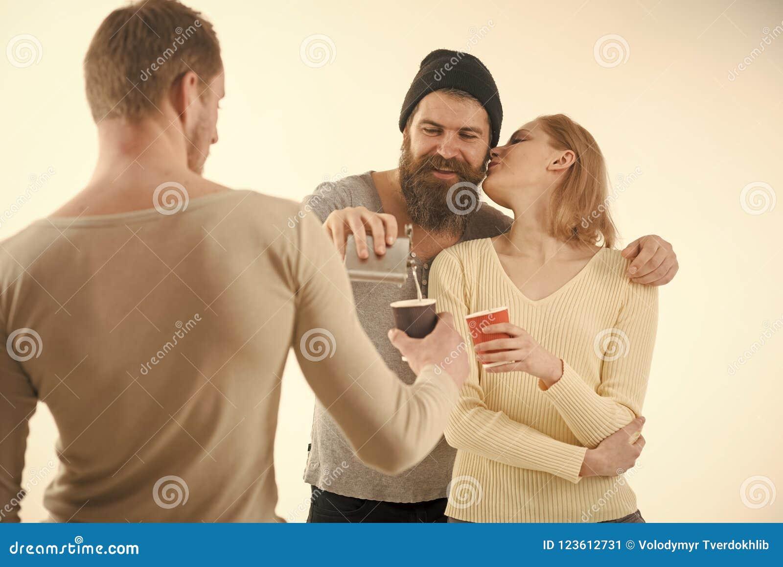 Компания жизнерадостных друзей тратит отдых с пить Парни держат чашку, склянку с спиртом, говорят Концепция потехи и отдыха