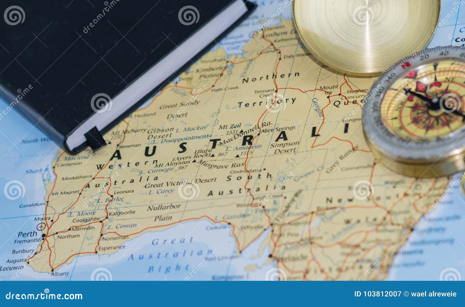 Компас на конце вверх по карте указывая на Австралию и планируя назначение перемещения с примечаниями путешественника в фото