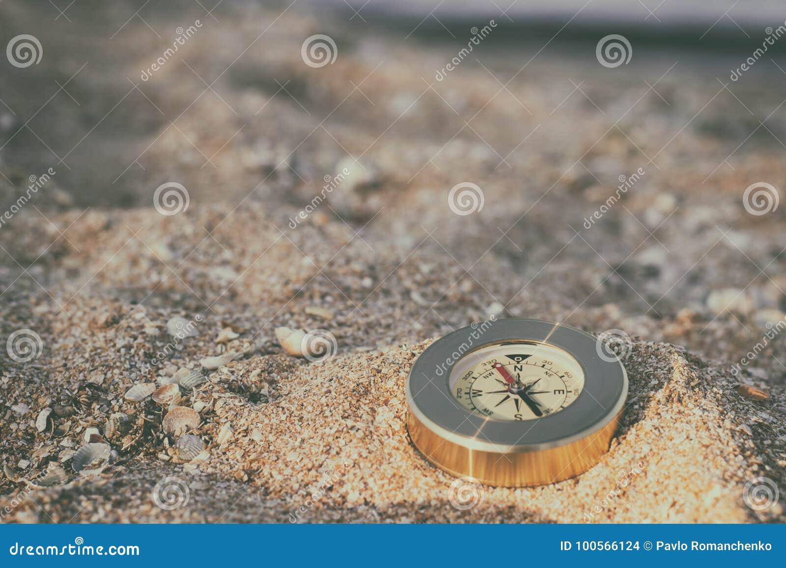 Компас показывая направление лежит на песке моря с раковинами