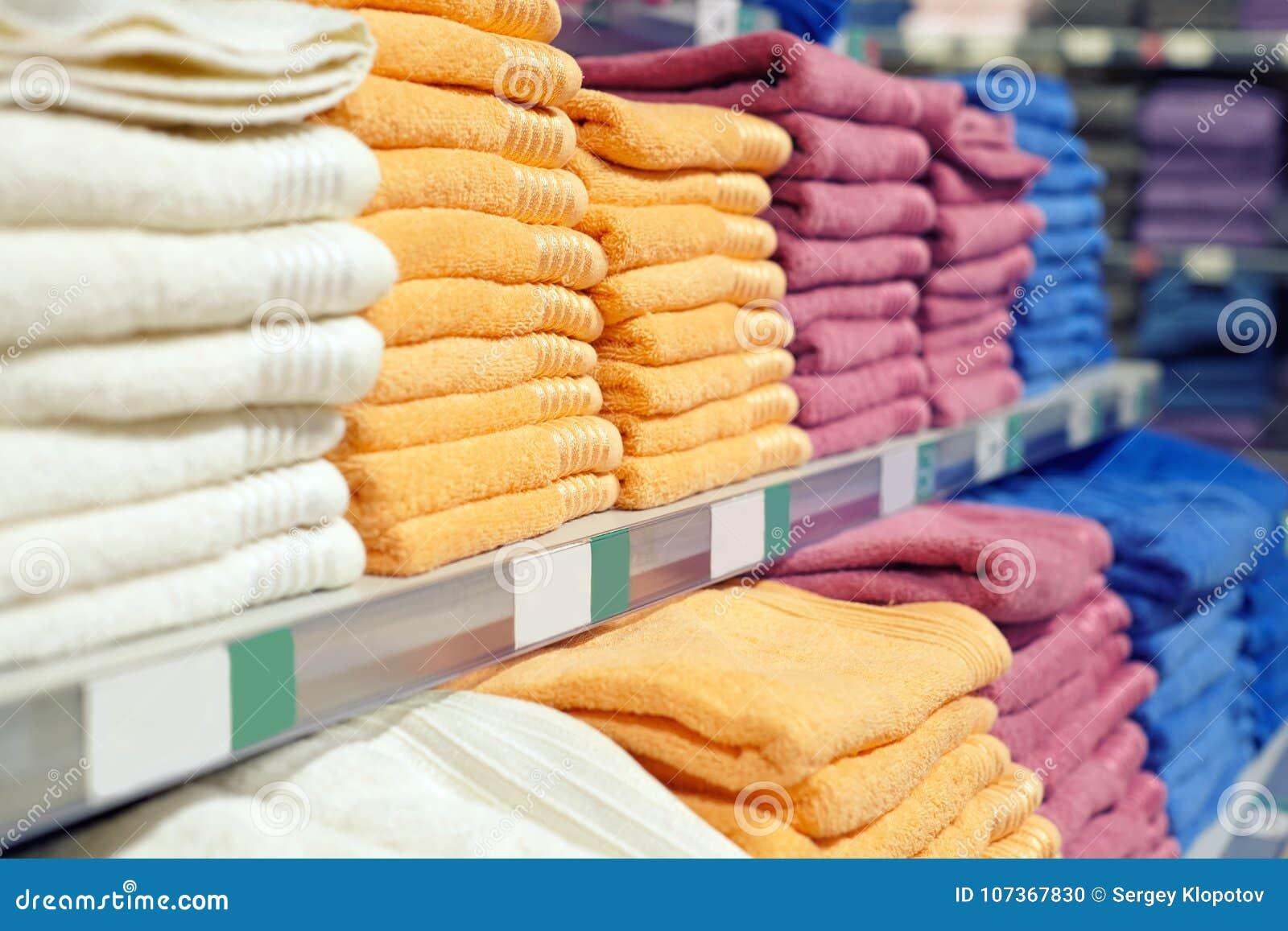 Комплект покрашенных полотенец на полке в магазине