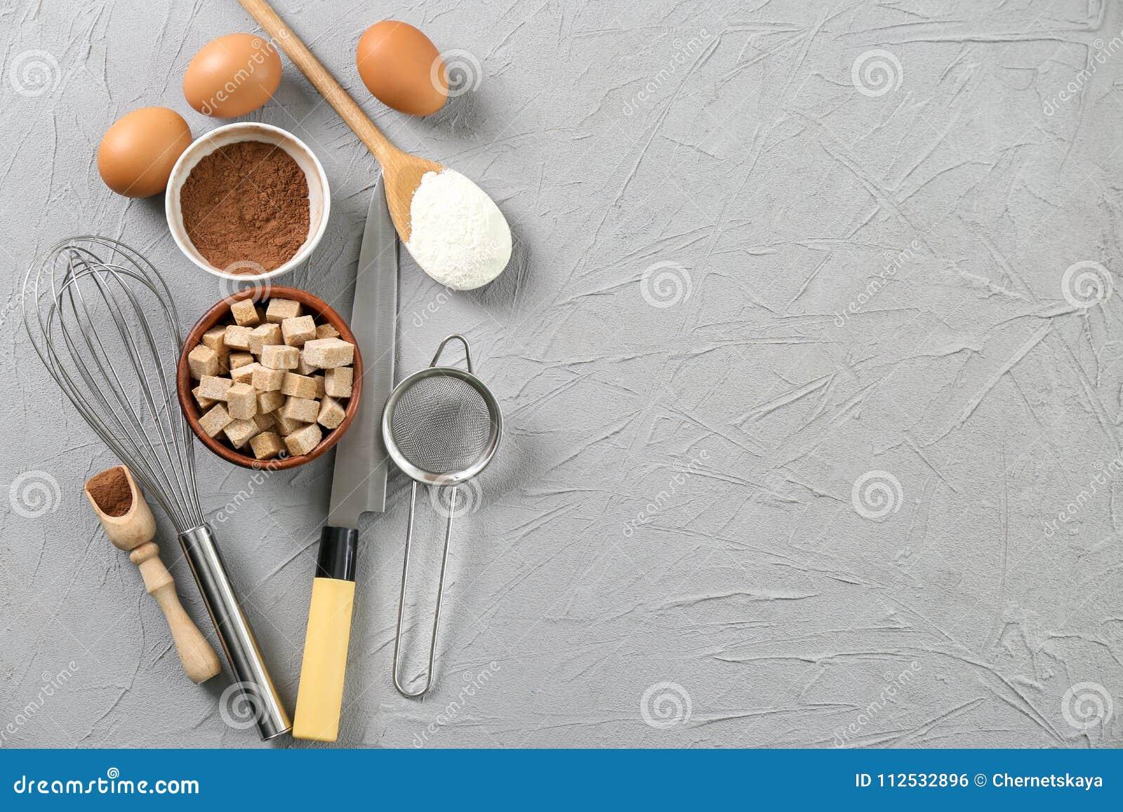 Комплект kitchenware и продуктов на серой предпосылке