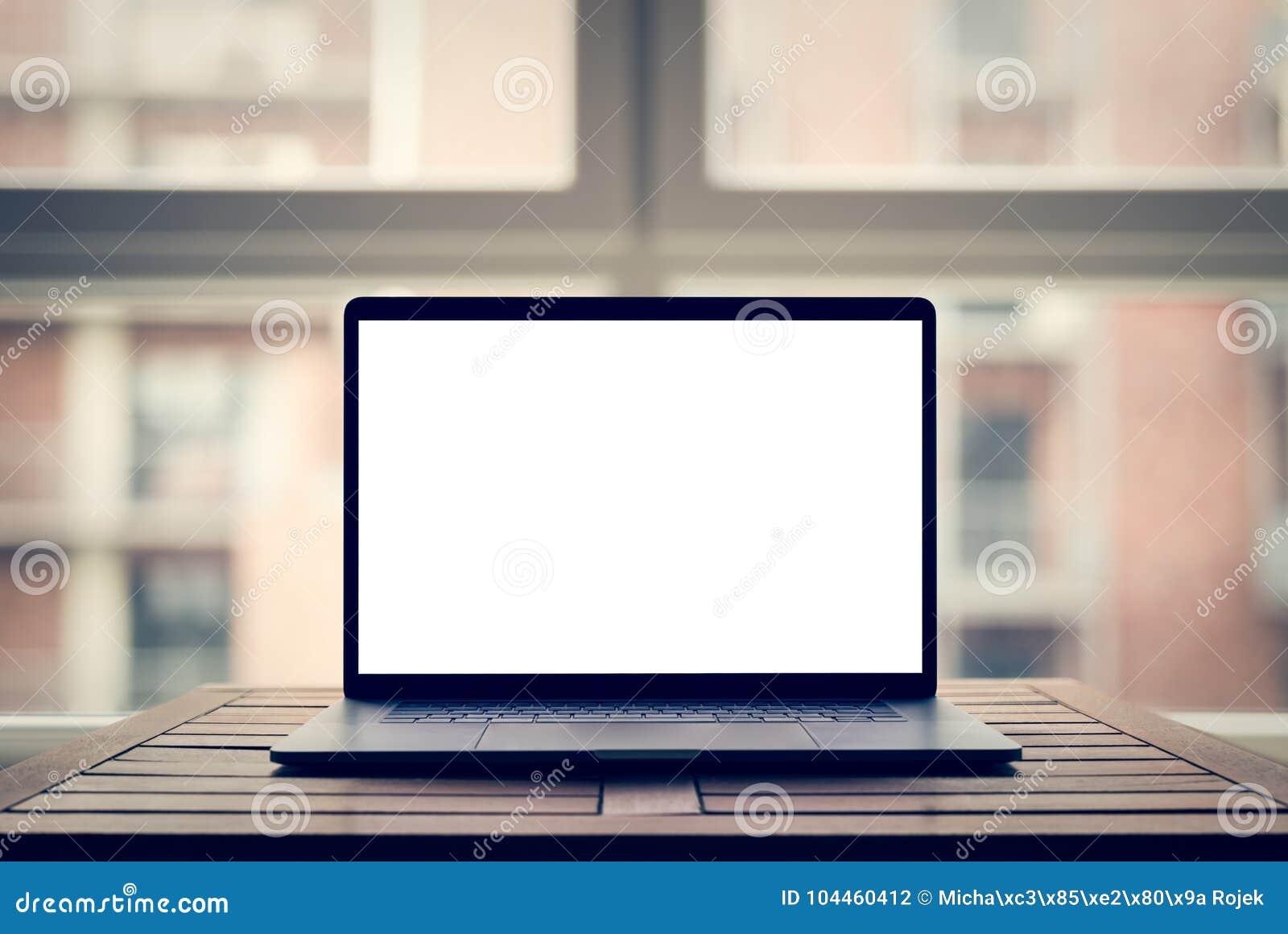 Компьтер-книжка с пустым экраном на таблице в современной просторной квартире