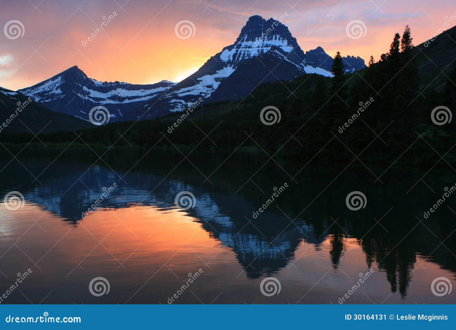 Стремительное настоящее озеро на национальном парке ледника захода солнца